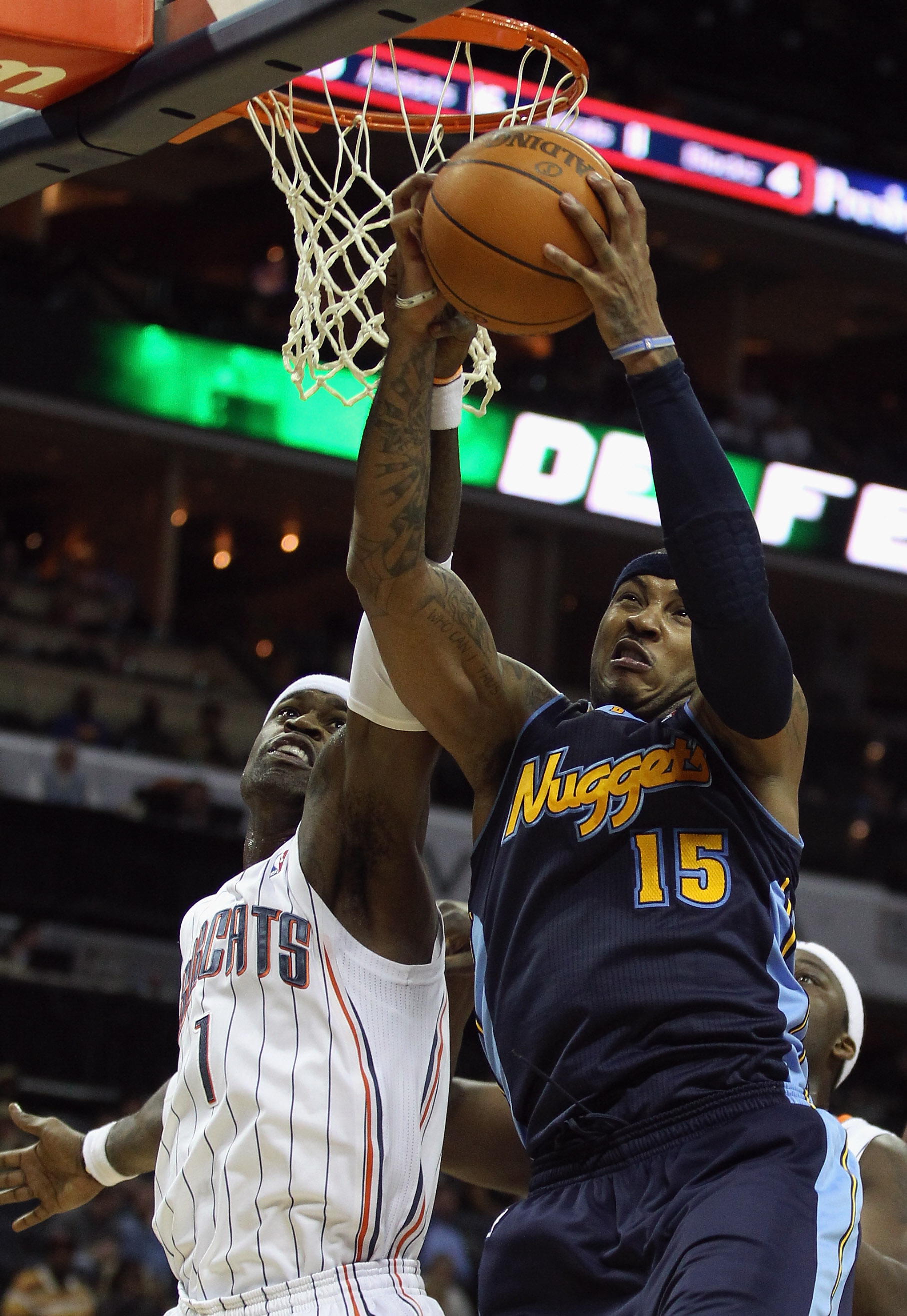 CHARLOTTE, NC - DECEMBER 07:  Carmelo Anthony #15 of the Denver Nuggets grabs a rebound over Stephen Jackson #1 of the Charlotte Bobcats during their game at Time Warner Cable Arena on December 7, 2010 in Charlotte, North Carolina.  NOTE TO USER: User exp