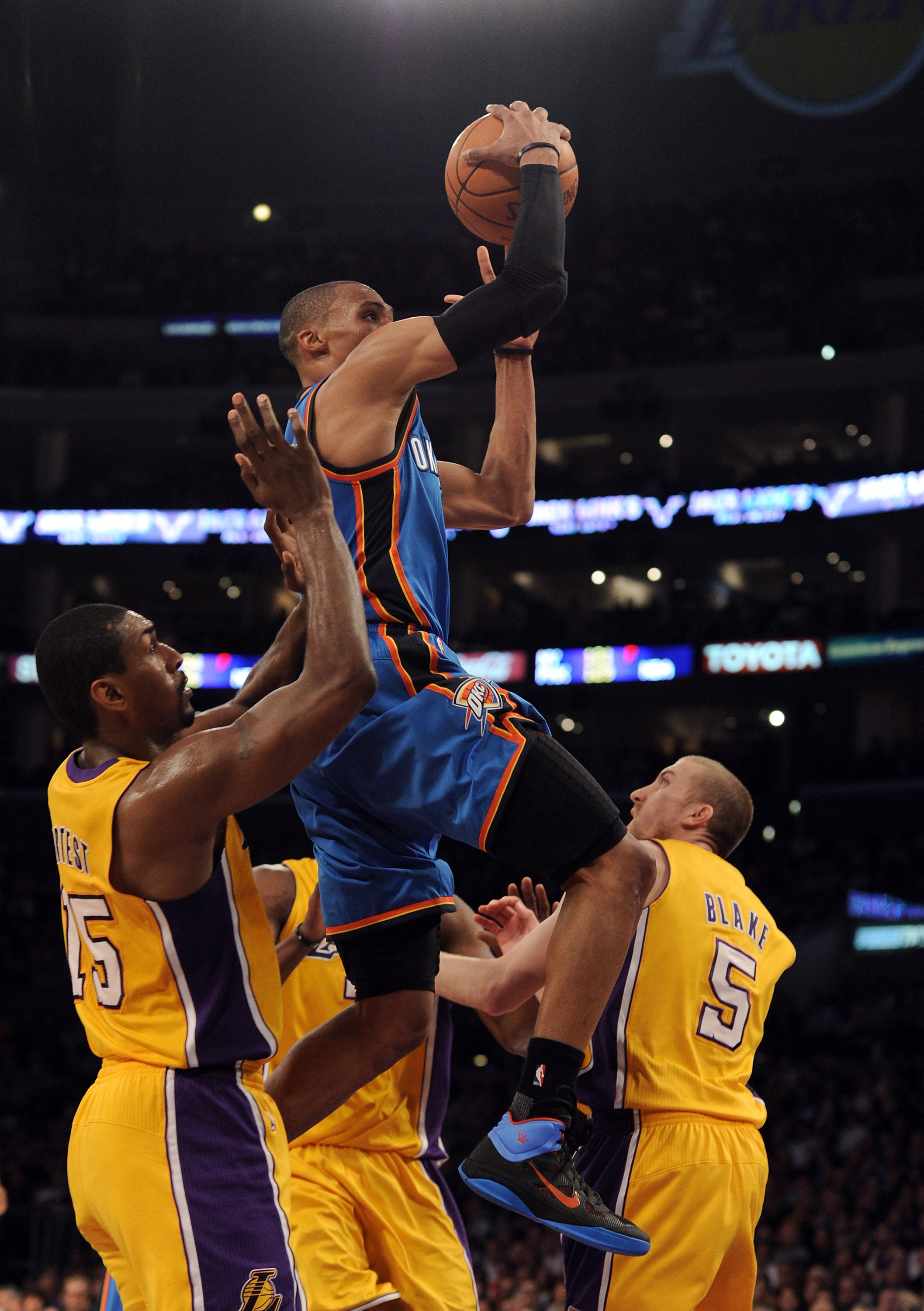 LOS ANGELES, CA - JANUARY 17:  Russell Westbrook #0 of the Oklahoma City Thunder scores on a layup between Ron Artest #15 and Steve Blake #5 of the Los Angeles Lakers during a 101-94 Laker win at the Staples Center on January 17, 2011 in Los Angeles, Cali