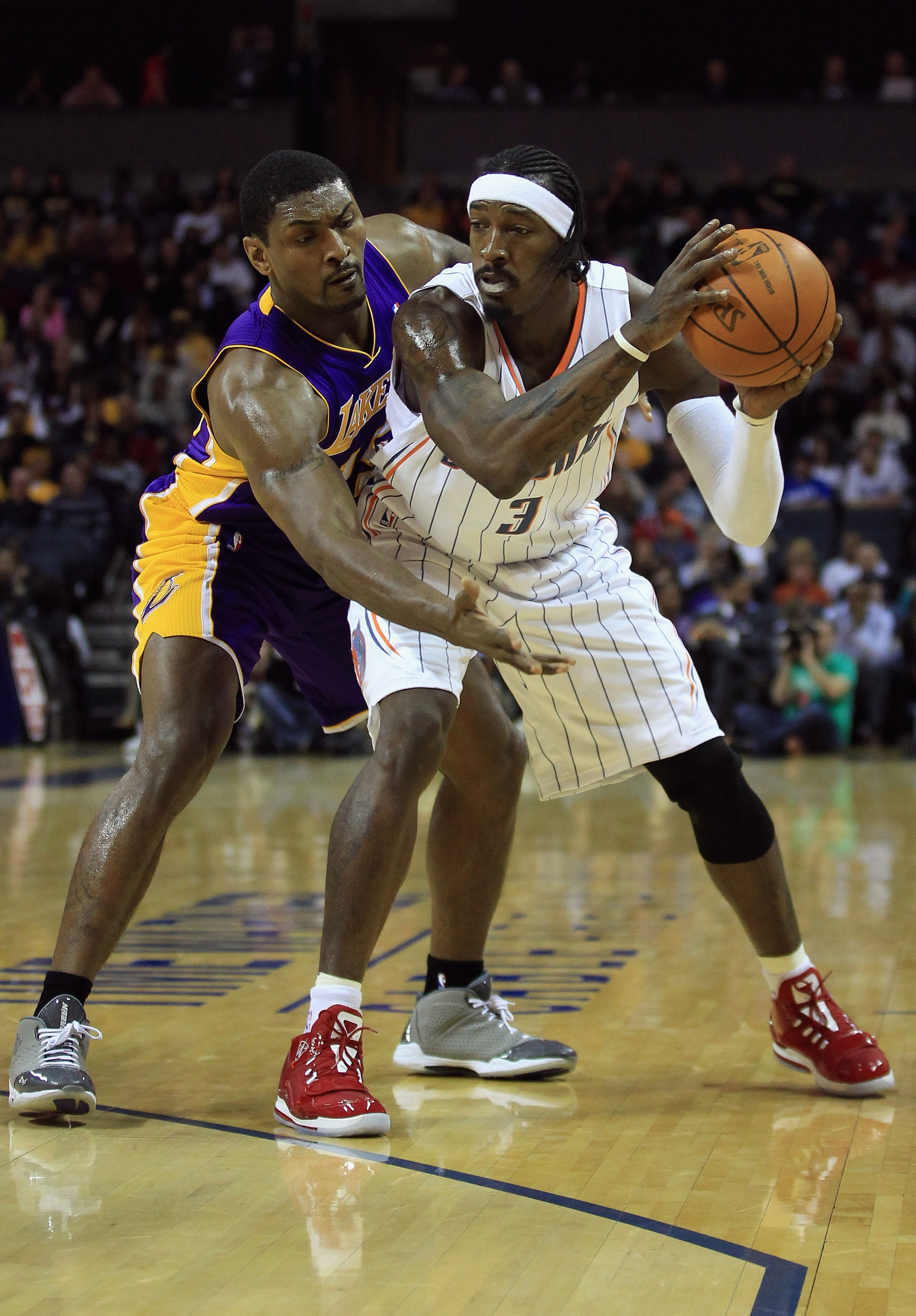 CHARLOTTE, NC - FEBRUARY 14:  Ron Artest #15 of the Los Angeles Lakers reaches for the ball against Gerald Wallace #3 of the Charlotte Bobcats during their game at Time Warner Cable Arena on February 14, 2011 in Charlotte, North Carolina. NOTE TO USER: Us