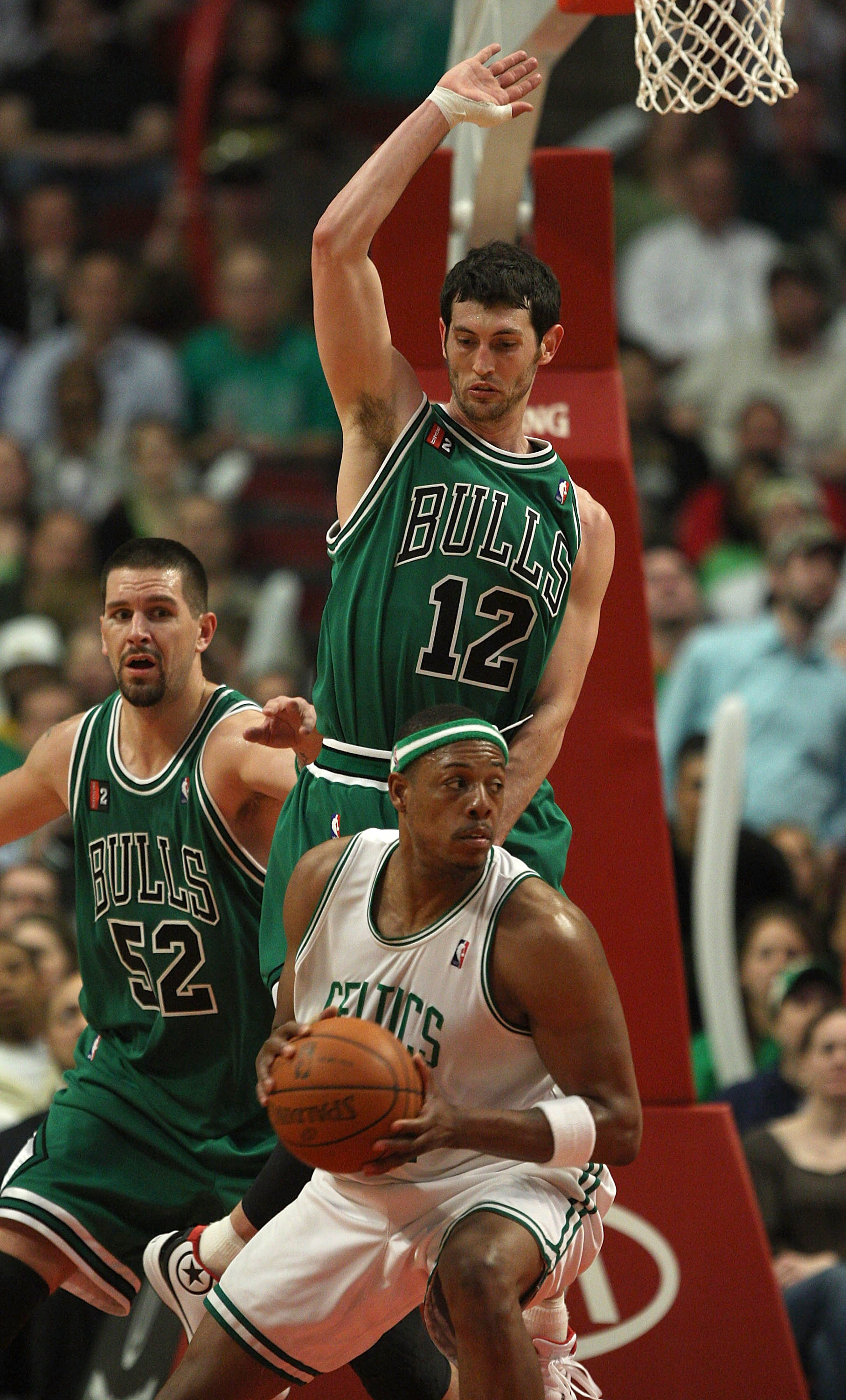 CHICAGO - MARCH 17: Kirk Hinrich #12 of the Chicago Bulls jumps to defend against Paul Pierce #34 of the Boston Celtics as Brad Miller #52 assists on March 17, 2009 at the United Center in Chicago, Illinois. The Bulls defeated the Celtics 127-121. NOTE TO