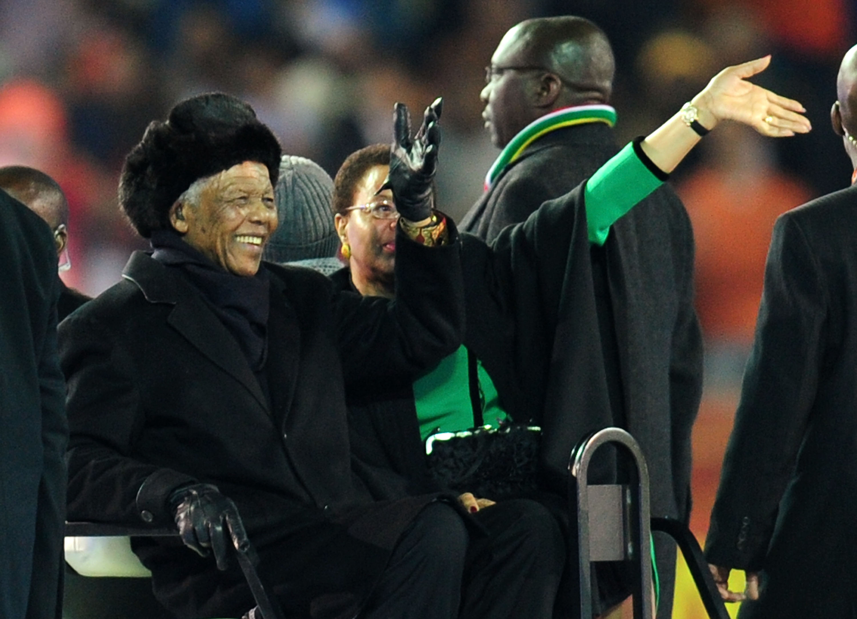 JOHANNESBURG, SOUTH AFRICA - JULY 11:  Former South Africa President Nelson Mandela and wife Graca Machel wave to the crowds prior to the 2010 FIFA World Cup South Africa Final match between Netherlands and Spain at Soccer City Stadium on July 11, 2010 in