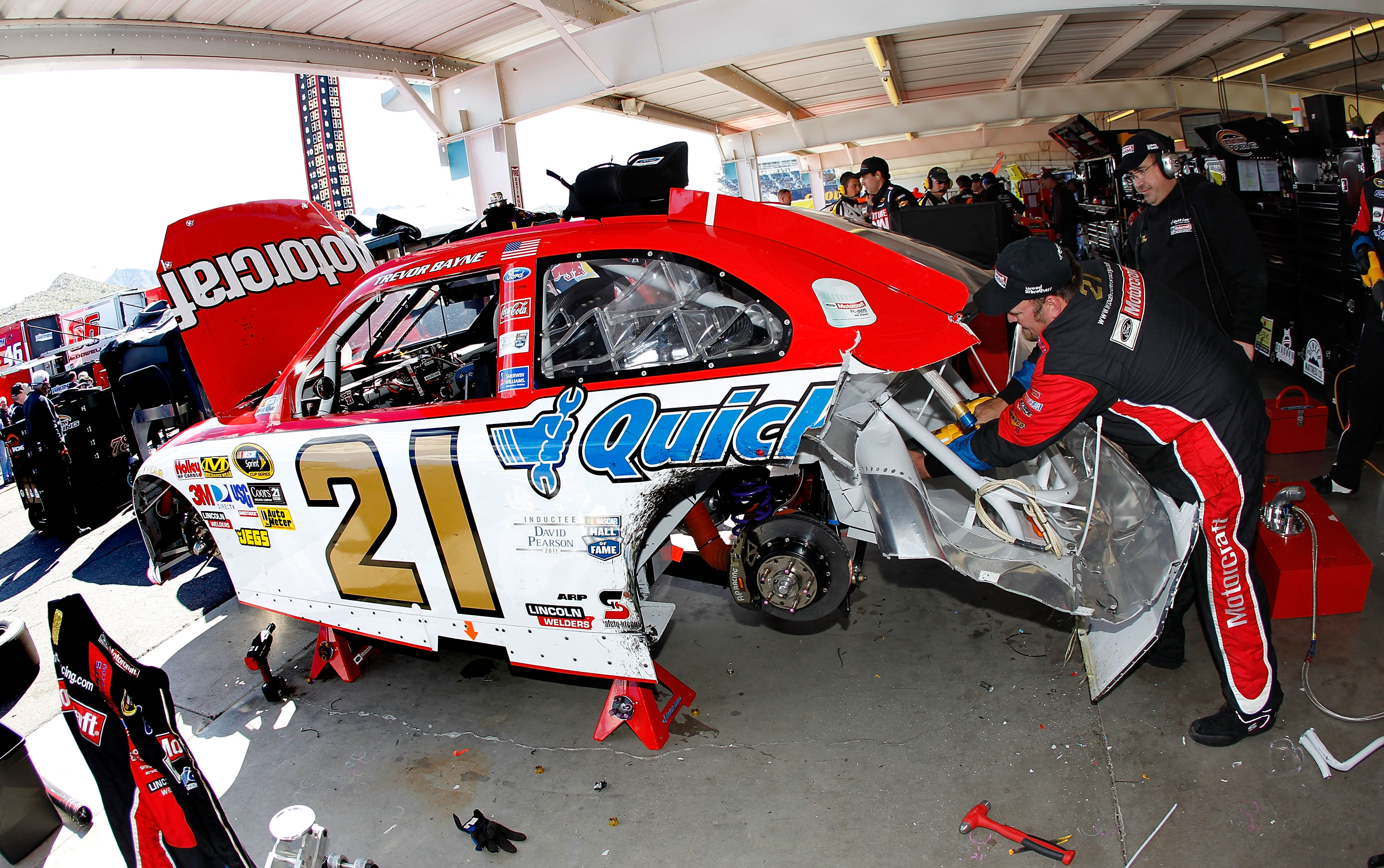 AVONDALE, AZ - FEBRUARY 27:  Crew members work on the car Trevor Bayne, driver of the #21 Motorcraft/Quick Lane Ford, after Bayne crashed during the NASCAR Sprint Cup Series Subway Fresh Fit 500 at Phoenix International Raceway on February 27, 2011 in Avo