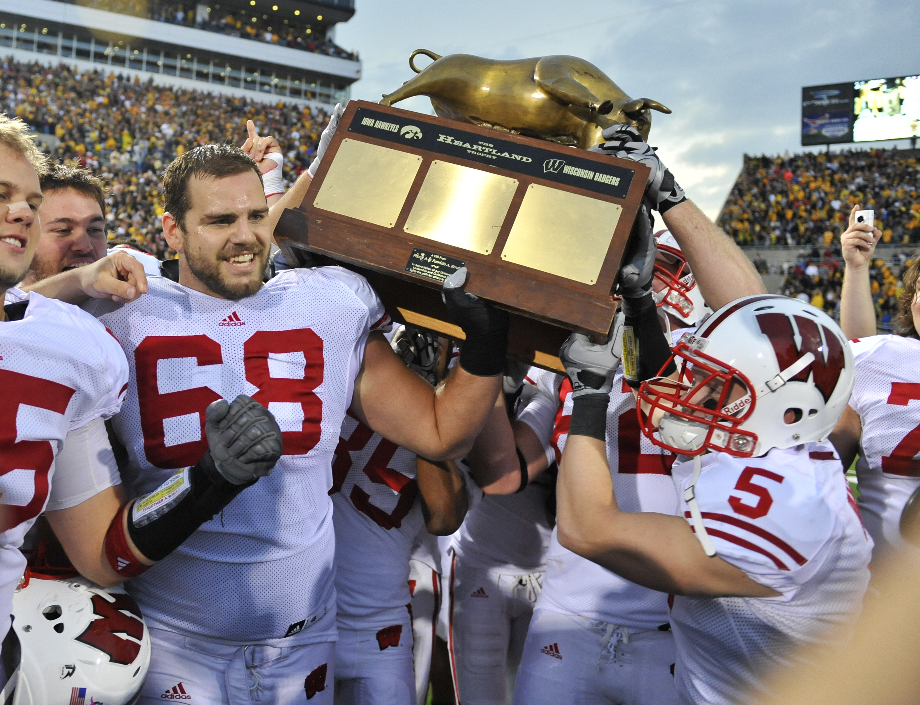 IOWA CITY, IA - OCTOBER 23: Offensive lineman Gabe Carimi #68 for the Wisconsin Badger holds the Heartland Trophy with his teammates as they celebrate their victory of the University of Iowa Hawkeyes at Kinnick Stadium on October 23, 2010 in Iowa City, Io