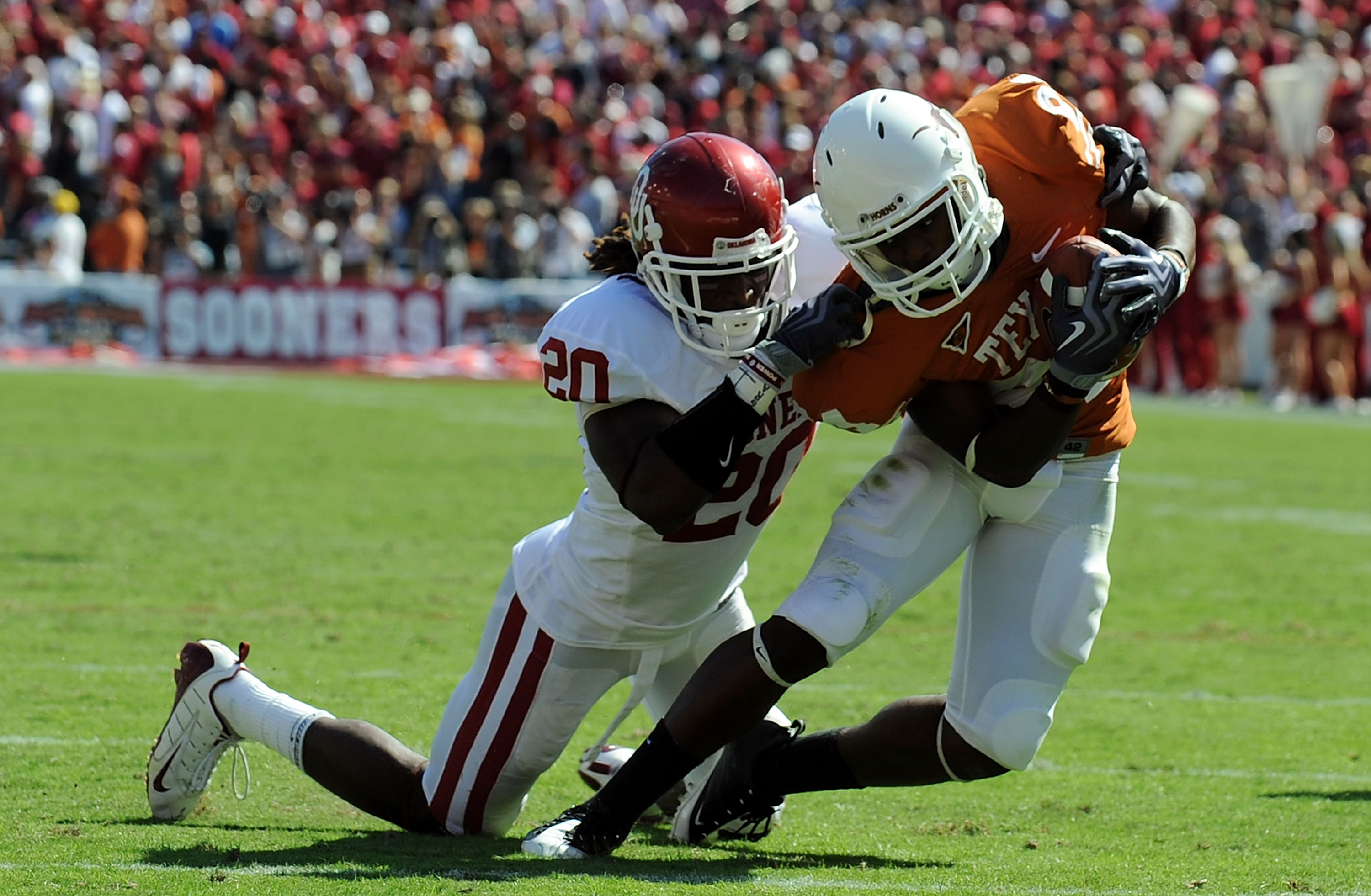 DALLAS - OCTOBER 17:  Wide receiver Marquise Goodwin #84 of the Texas Longhorns runs for a touchdown against Quinton Carter #20 of the Oklahoma Sooners at Cotton Bowl on October 17, 2009 in Dallas, Texas.  (Photo by Ronald Martinez/Getty Images)