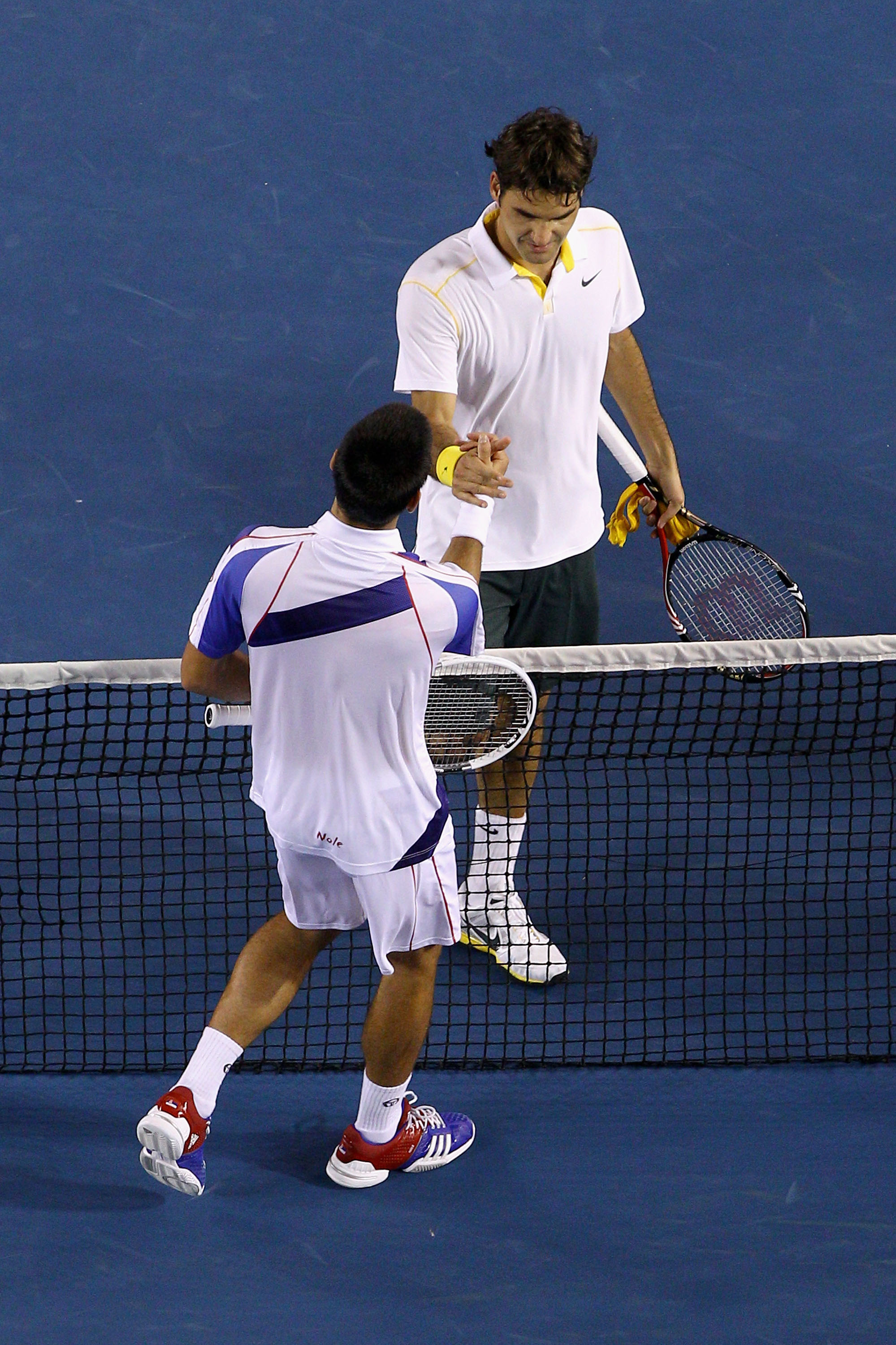 MELBOURNE, AUSTRALIA - JANUARY 27:  Roger Federer of Switzerland congratulates Novak Djokovic of Serbia after their semifinal match during day eleven of the 2011 Australian Open at Melbourne Park on January 27, 2011 in Melbourne, Australia.  (Photo by Qui