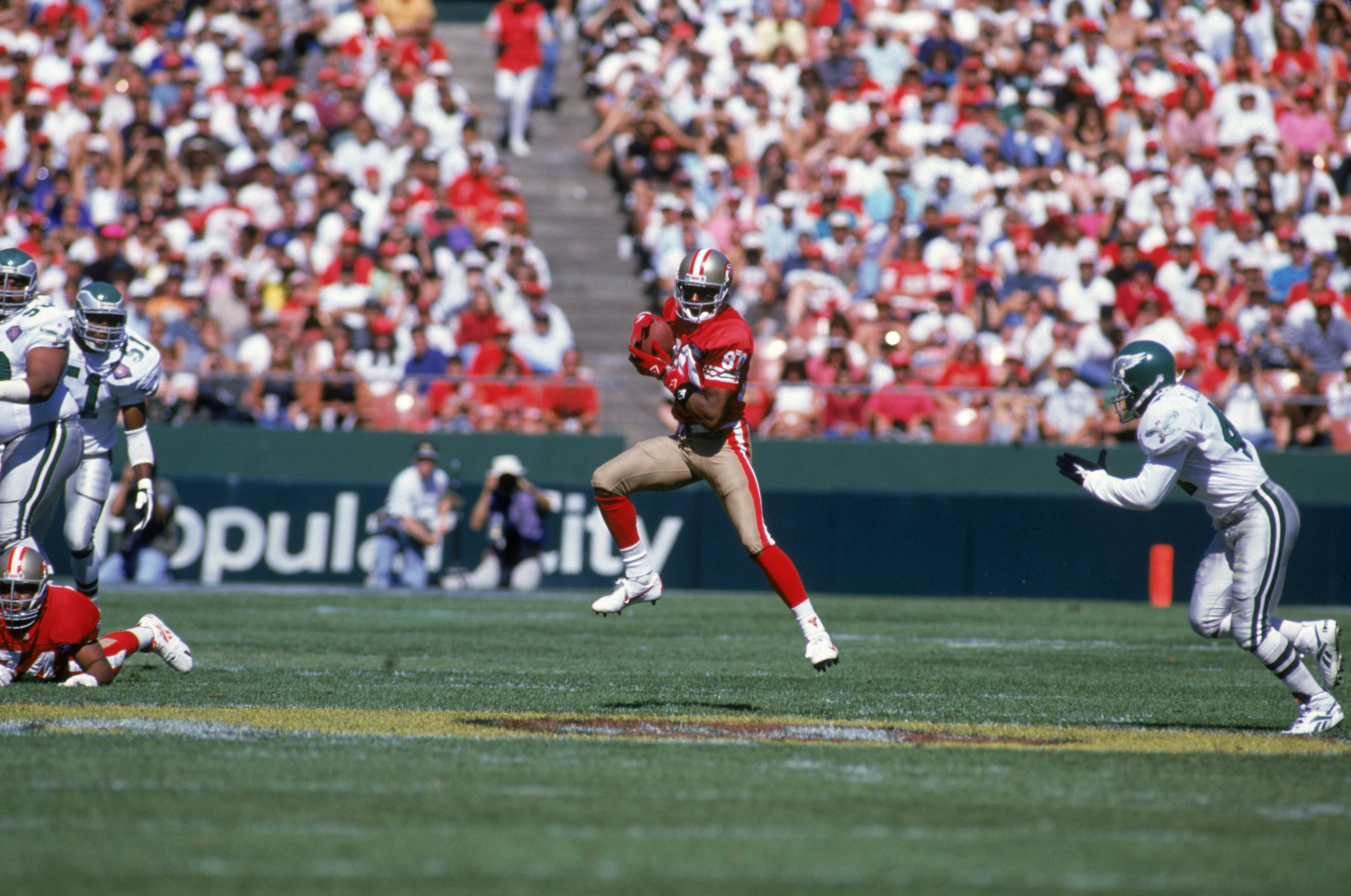 SAN FRANCISCO - OCTOBER 2:  Wide receiver Jerry Rice #80 of the San Francisco 49ers finds room to run against Philadelphia Eagles defense during a game at Candlestick Park on October 2, 1994 in San Francisco, California.  The Eagles won 40-8.  (Photo by G