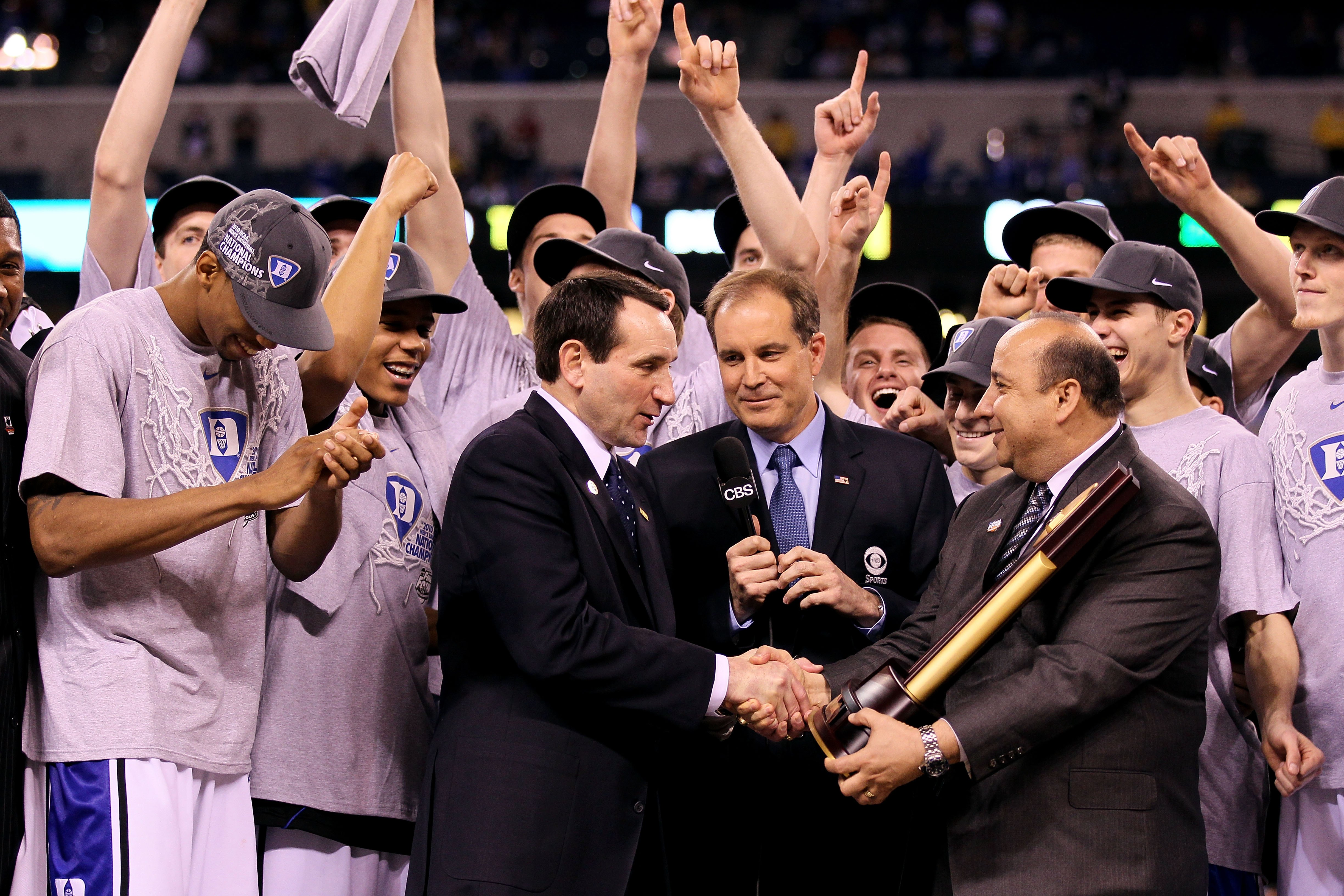 INDIANAPOLIS - APRIL 05:  Head coach Mike Krzyzewski of the Duke Blue Devils receives the trophy as his players celebrate after they won 61-59 against the Butler Bulldogs during the 2010 NCAA Division I Men's Basketball National Championship game at Lucas