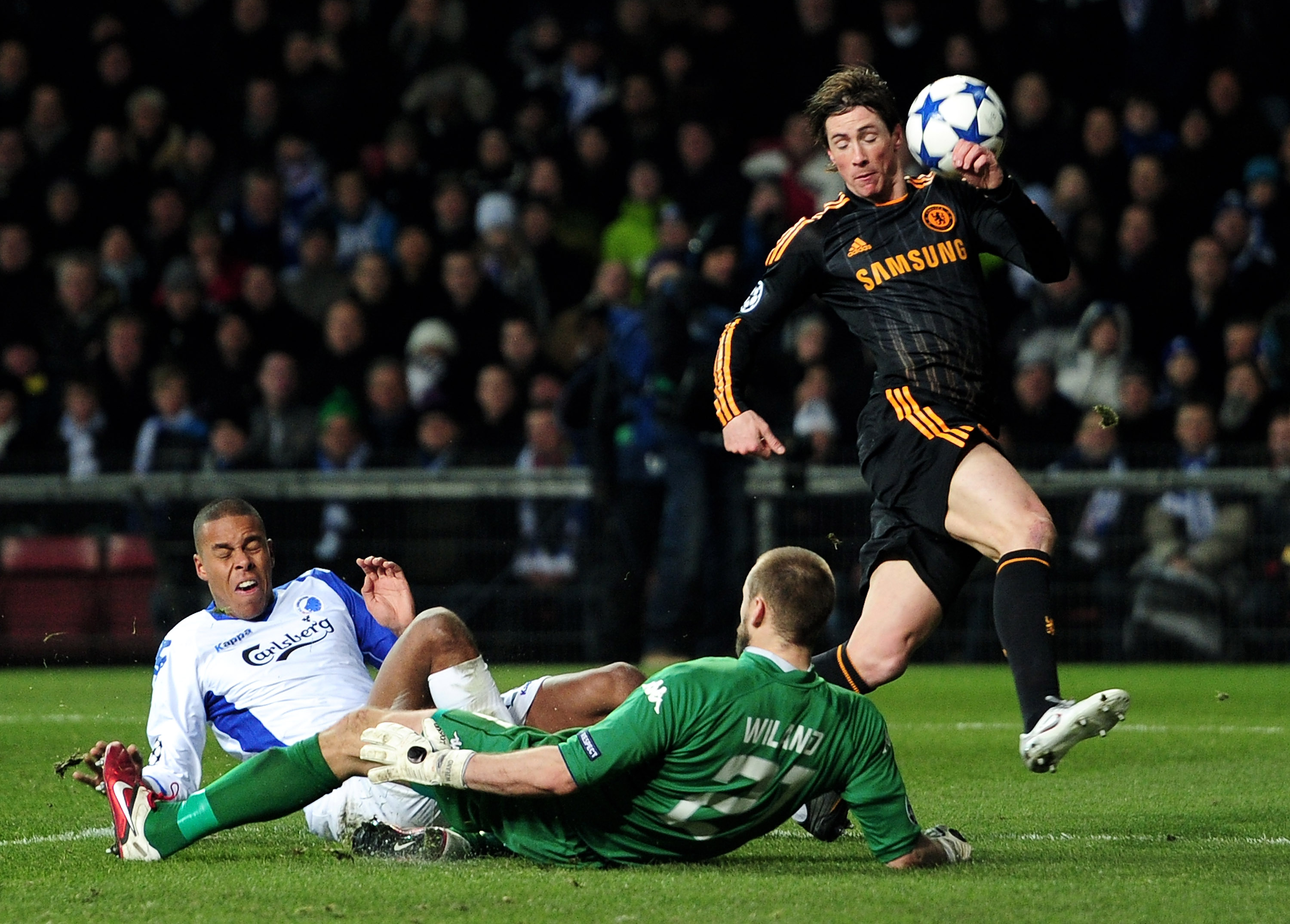 COPENHAGEN, DENMARK - FEBRUARY 22:  Fernando Torres of Chelsea is challenged by Mathias Zanka Jorgensen (L) and Johan Wiland of FC Copenhagen during  the UEFA Champions League round of 16 first leg match between FC Copenhagen and Chelsea at Parken Stadium