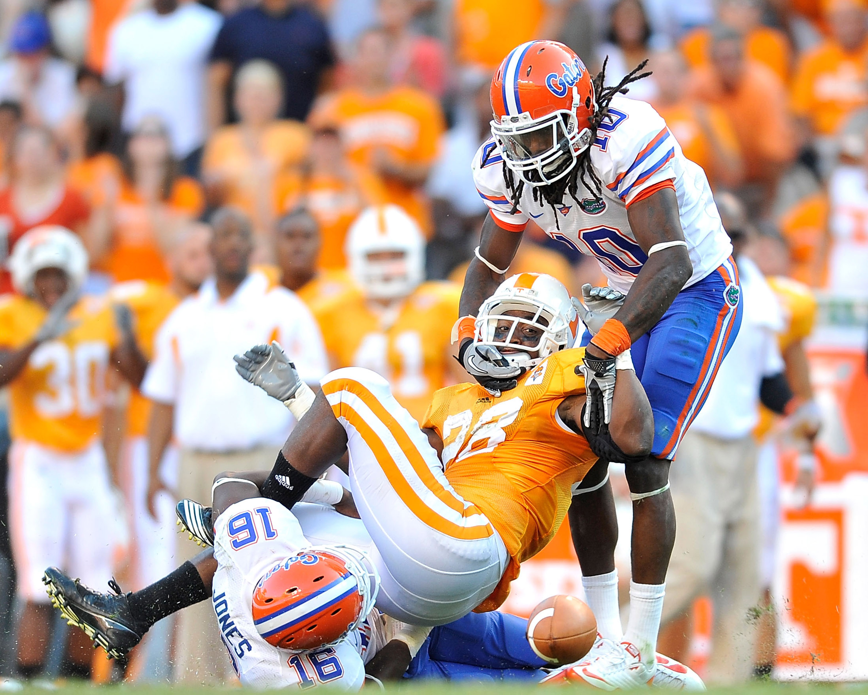 KNOXVILLE, TN - SEPTEMBER 18:  Will Hill #10 and A.J. Jones #16 of the Florida Gators force a fumble by Tauren Poole #28 of the Tennessee Volunteers late in the fourth quarter at Neyland Stadium on September 18, 2010 in Knoxville, Tennessee. Florida won 3