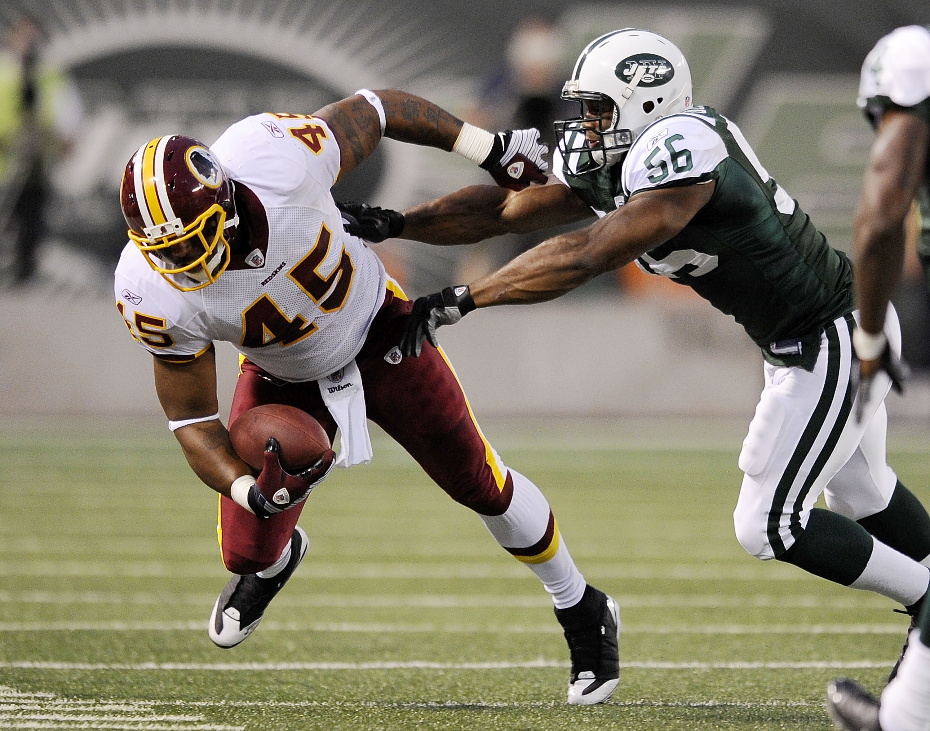 EAST RUTHERFORD, NJ - AUGUST 16:  Vernon Gholston #56 of the New York Jets  takes down Mike Sellers #45 of the Washington Redskins in a pre-season NFL game at Giants Stadium, August 16, 2008 in East Rutherford, New Jersey.  (Photo by Jeff Zelevansky/Getty