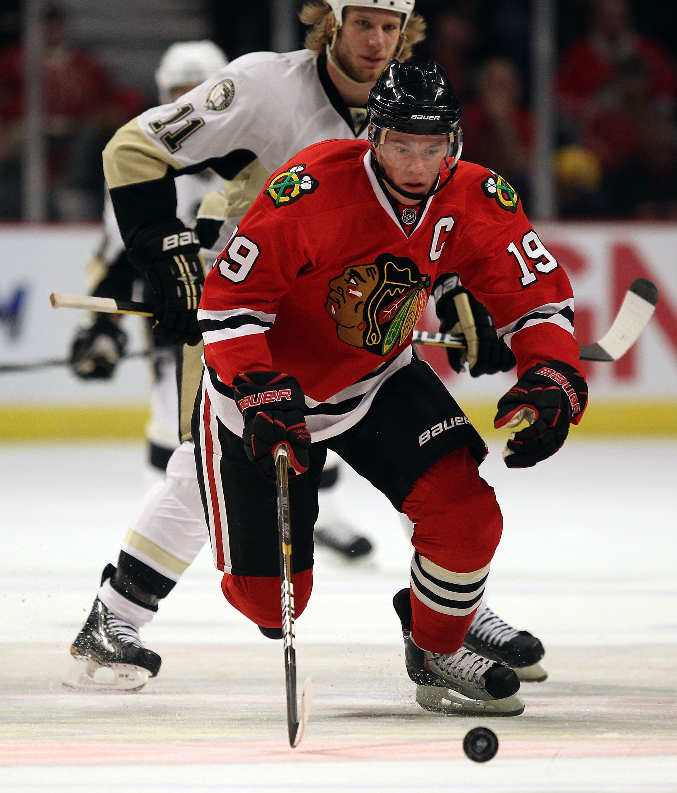 CHICAGO, IL - FEBRUARY 20: Jonathan Toews #19 of the Chicago Blackhawks chases down the puck in front of Jordan Staal #11 of the Pittsburgh Penguins at the United Center on February 20, 2011 in Chicago, Illinois. (Photo by Jonathan Daniel/Getty Images)