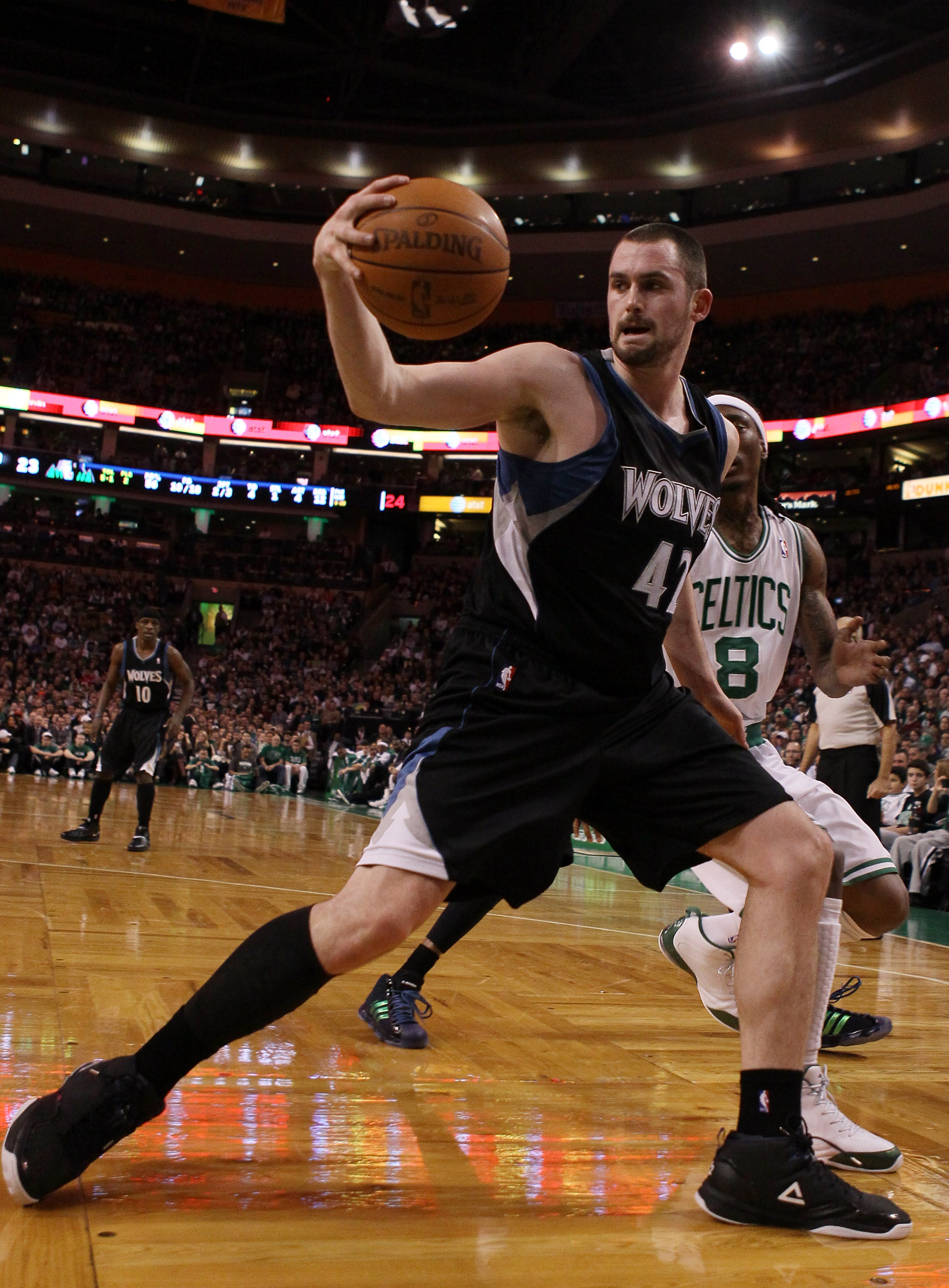 BOSTON, MA - JANUARY 03:  Kevin Love #42 of the Minnesota Timberwolves grabs the loose ball as Marquis Daniels #8 of the Boston Celtics defends on January 3, 2011 at the TD Garden in Boston, Massachusetts. NOTE TO USER: User expressly acknowledges and agr