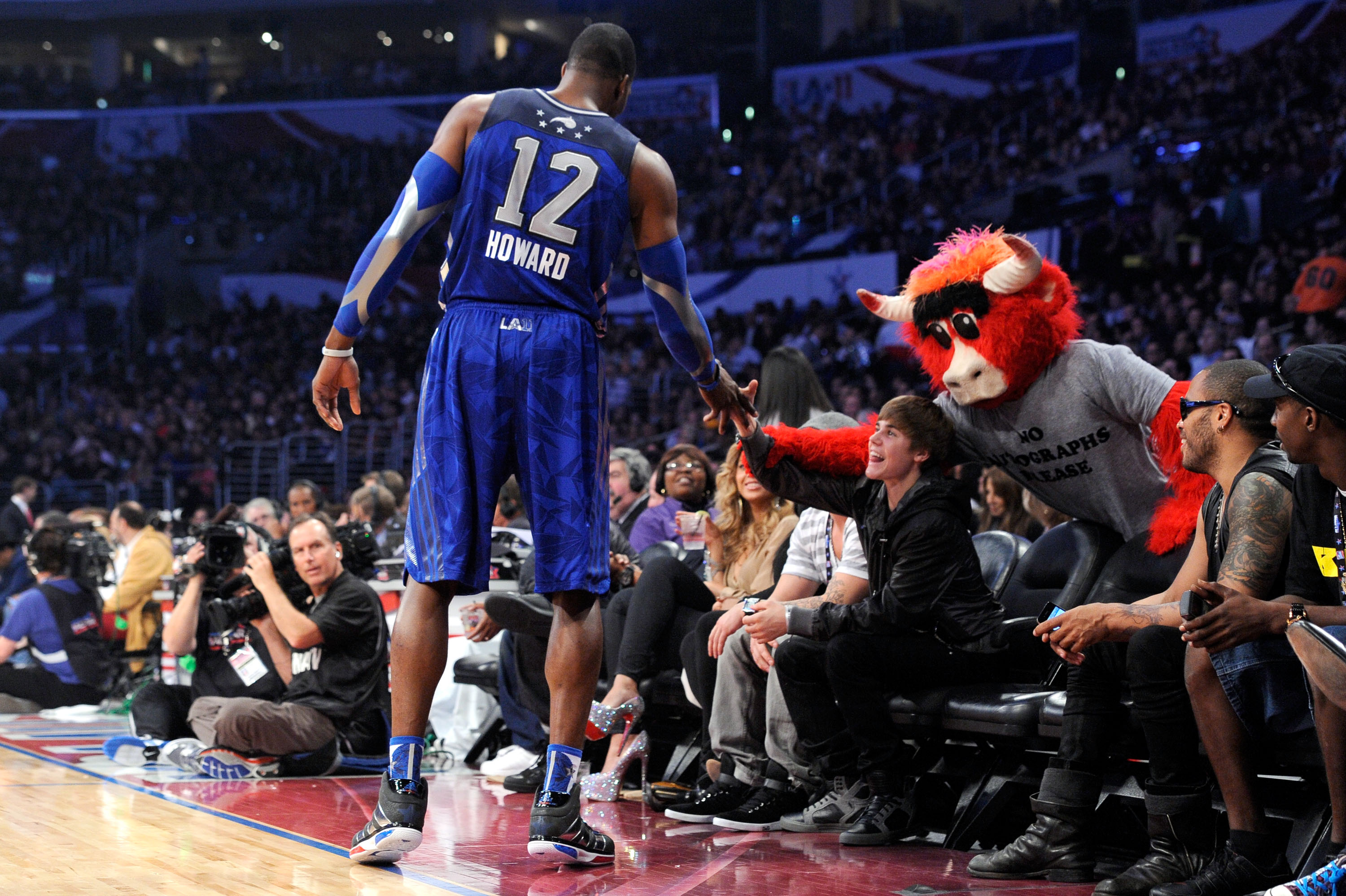 LOS ANGELES, CA - FEBRUARY 20:  (L-R) Dwight Howard #12 of the Orlando Magic and the Eastern Conference, singer Justin Bieber, and Chicago Bulls mascot 'Benny the Bull' courtside during the 2011 NBA All-Star game at Staples Center on February 20, 2011 in
