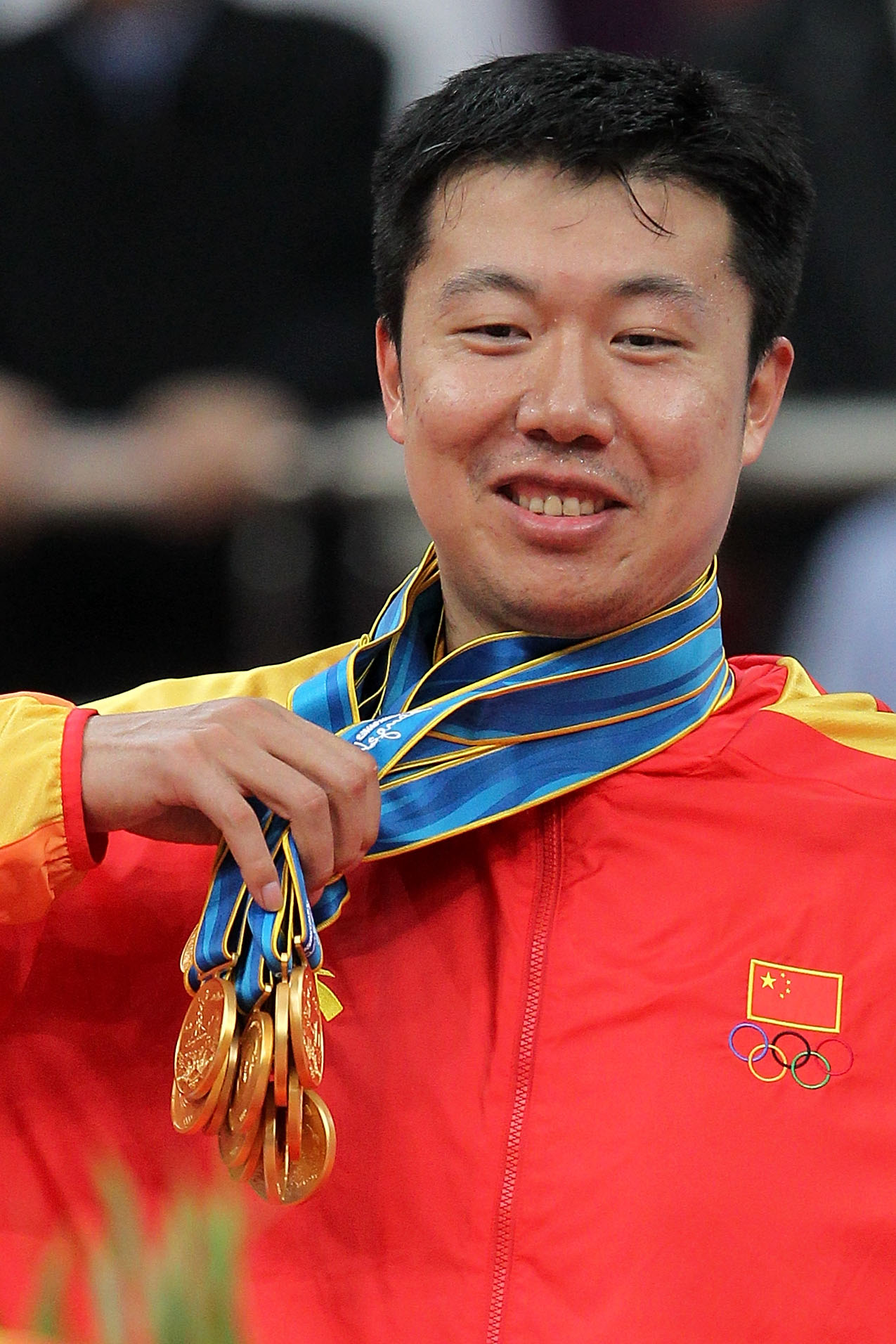 GUANGZHOU, CHINA - NOVEMBER 26:  Wang Zhizhi #14 of China is given all the medals by his teammates to wear after China wins the gold medal by defeating South Korea 77-71 in the men's gold medal basketball game at the Guangzhou International Sports Arena d