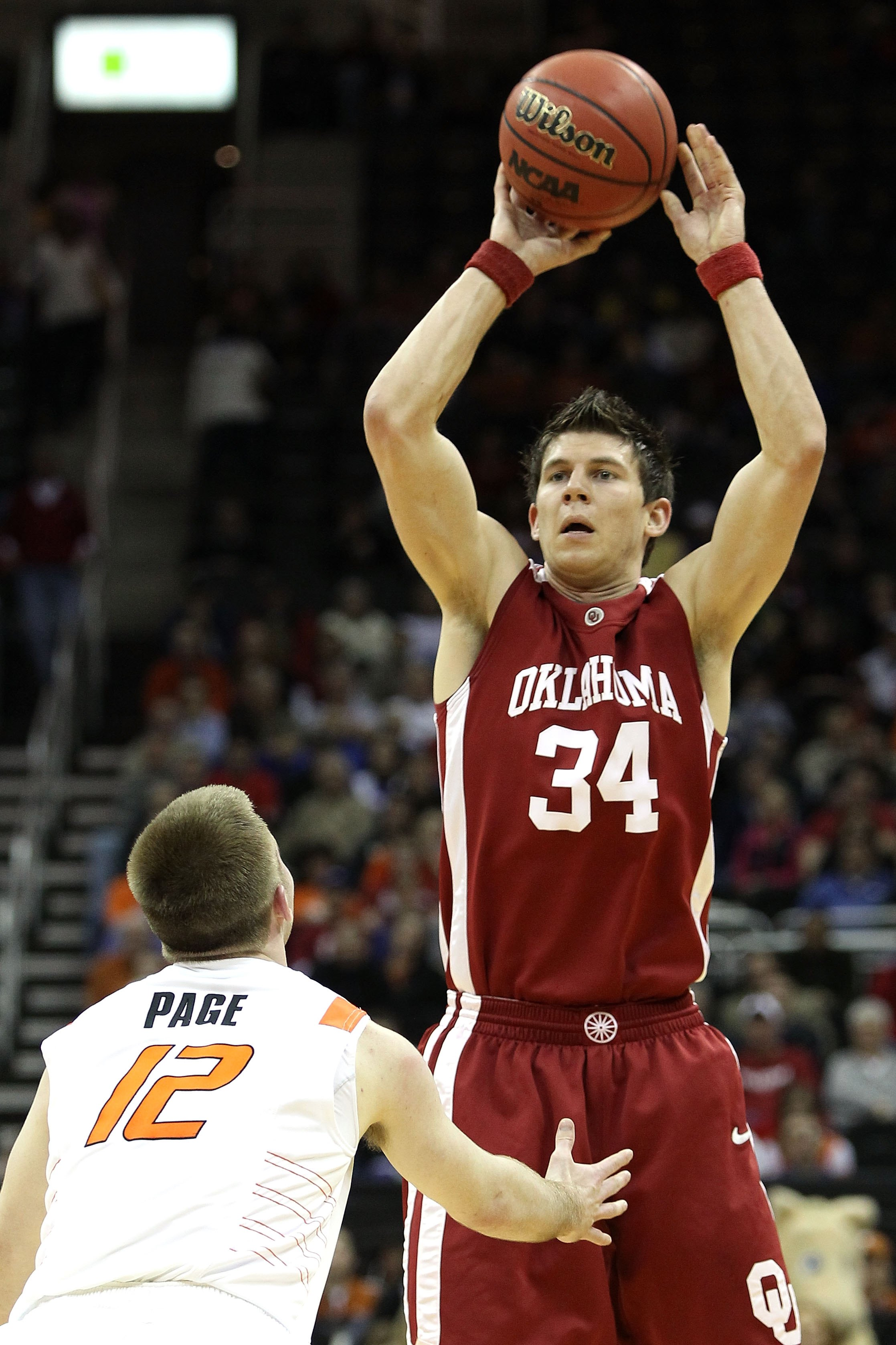 KANSAS CITY, MO - MARCH 10:  Cade Davis #34 of the Oklahoma Sooners moves the ball as he is covered by Keiton Page #12 of the Oklahoma State Cowboys during the first round game of the 2010 Phillips 66 Big 12 Men's Basketball Tournament at the Sprint Cente