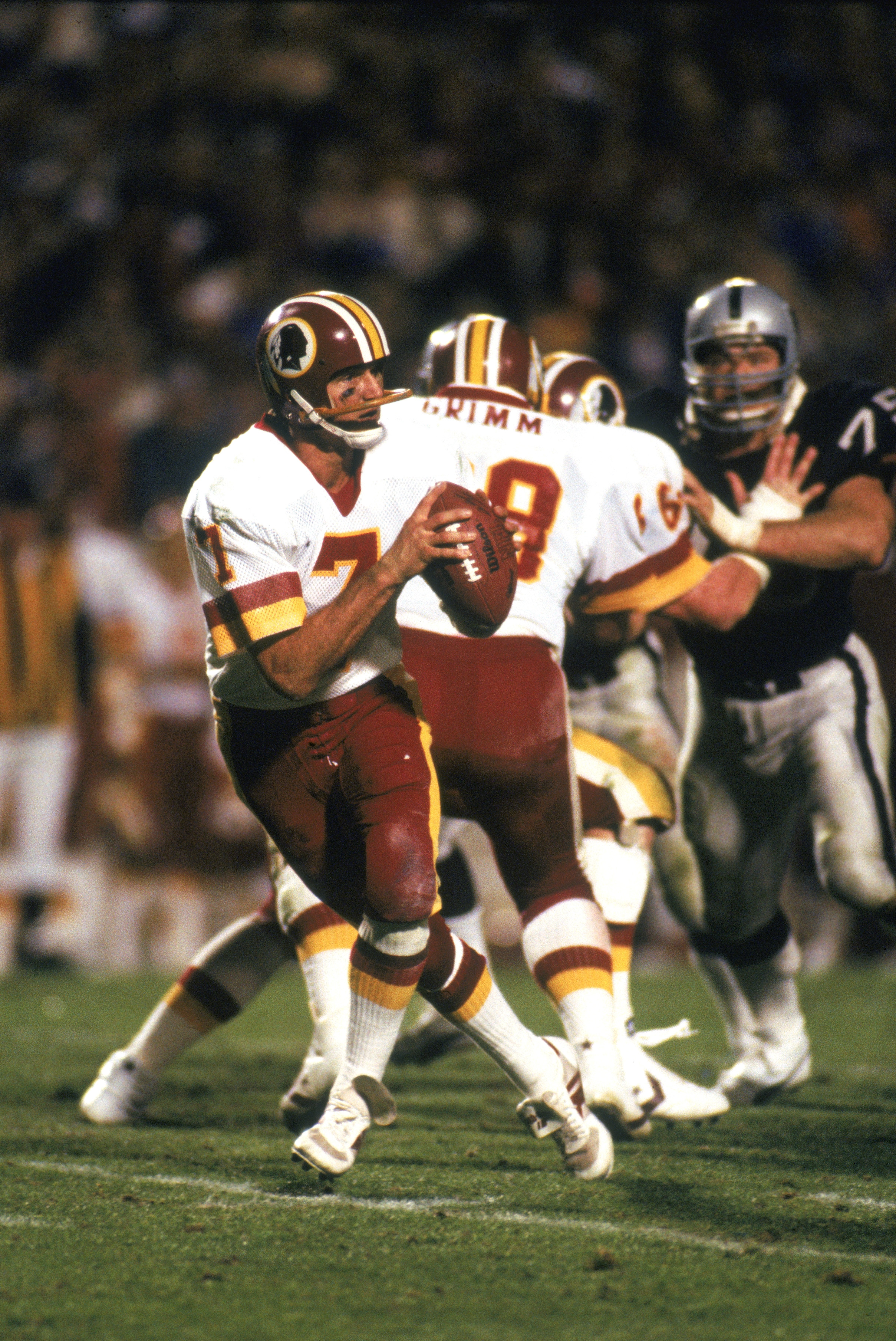 TAMPA, FL - JANUARY 22:  Joe Theismann #7 of the Washington Redskins moves back to pass during Super Bowl XVIII against the Los Angeles Raiders at Tampa Stadium on January 22, 1984 in Tampa, Florida. The Radiers defeated the Redskins 38-9. (Photo by: Gett