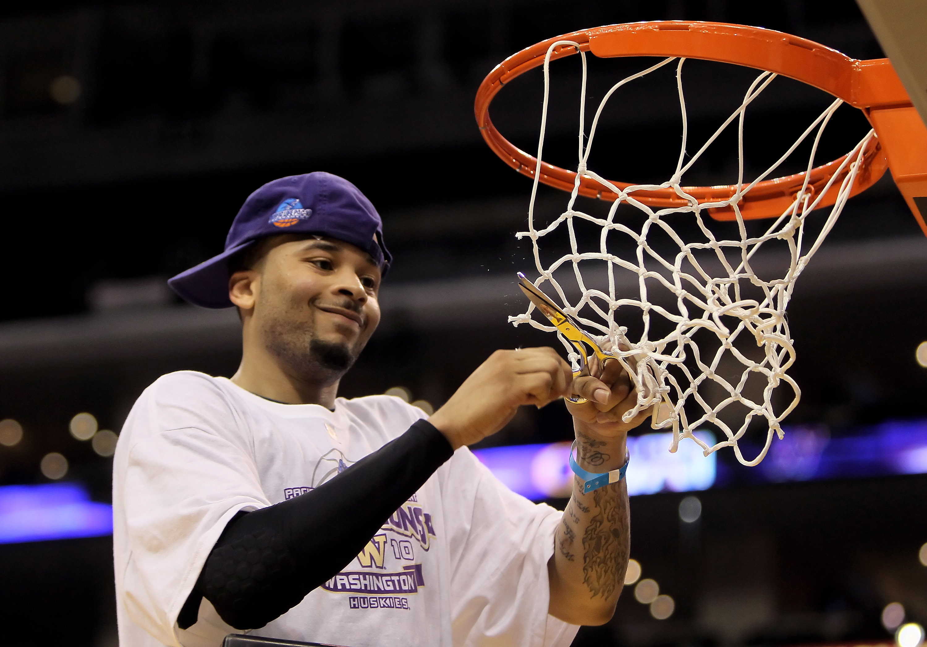LOS ANGELES, CA - MARCH 13:  Venoy Overton #1 of the Washington Huskies celebrates by cutting down the net following his teams victory over the Cal Golden Bears in the championship game of the Pac-10 Basketball Tournament at Staples Center on March 13, 20