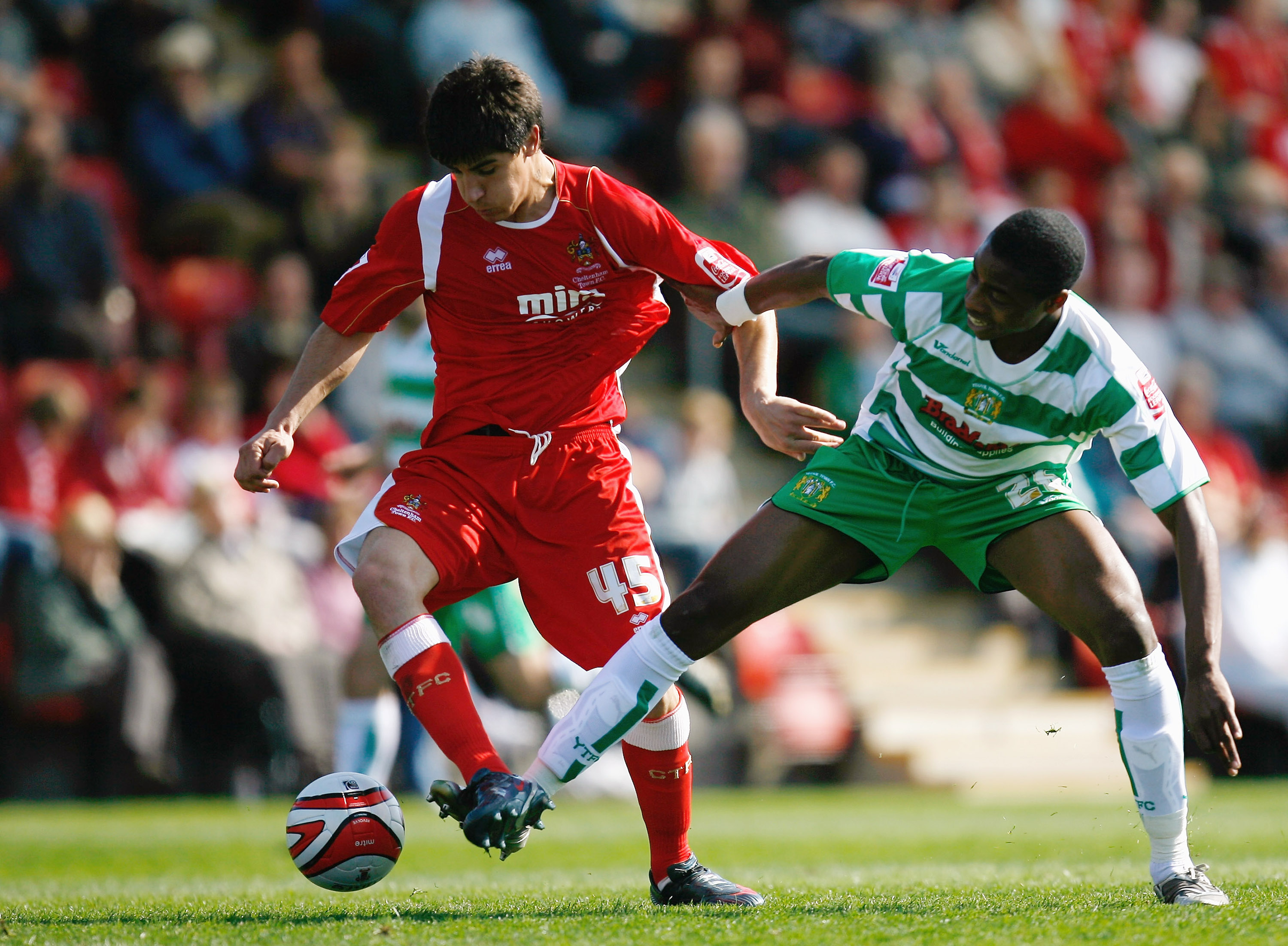 CHELTENHAM, UNITED KINGDOM - APRIL 13:  Jonathan Obika of Yeovil Town battles for the ball with Yuri Berchiche of Cheltenham Town during the Coca-Cola League One match between Cheltenham Town and Yeovil Town at Whaddon Road on April 13, 2009 in Cheltenham