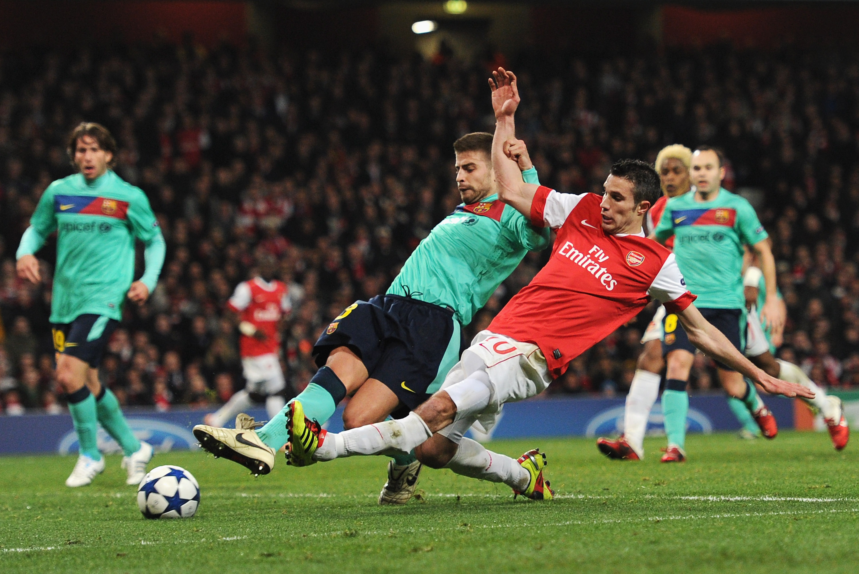 LONDON, ENGLAND - FEBRUARY 16:  Robin van Persie of Arsenal shoots at goal under a challenge by Gerard Pique of Barcelona during the UEFA Champions League round of 16 first leg match between Arsenal and Barcelona at the Emirates Stadium on February 16, 20