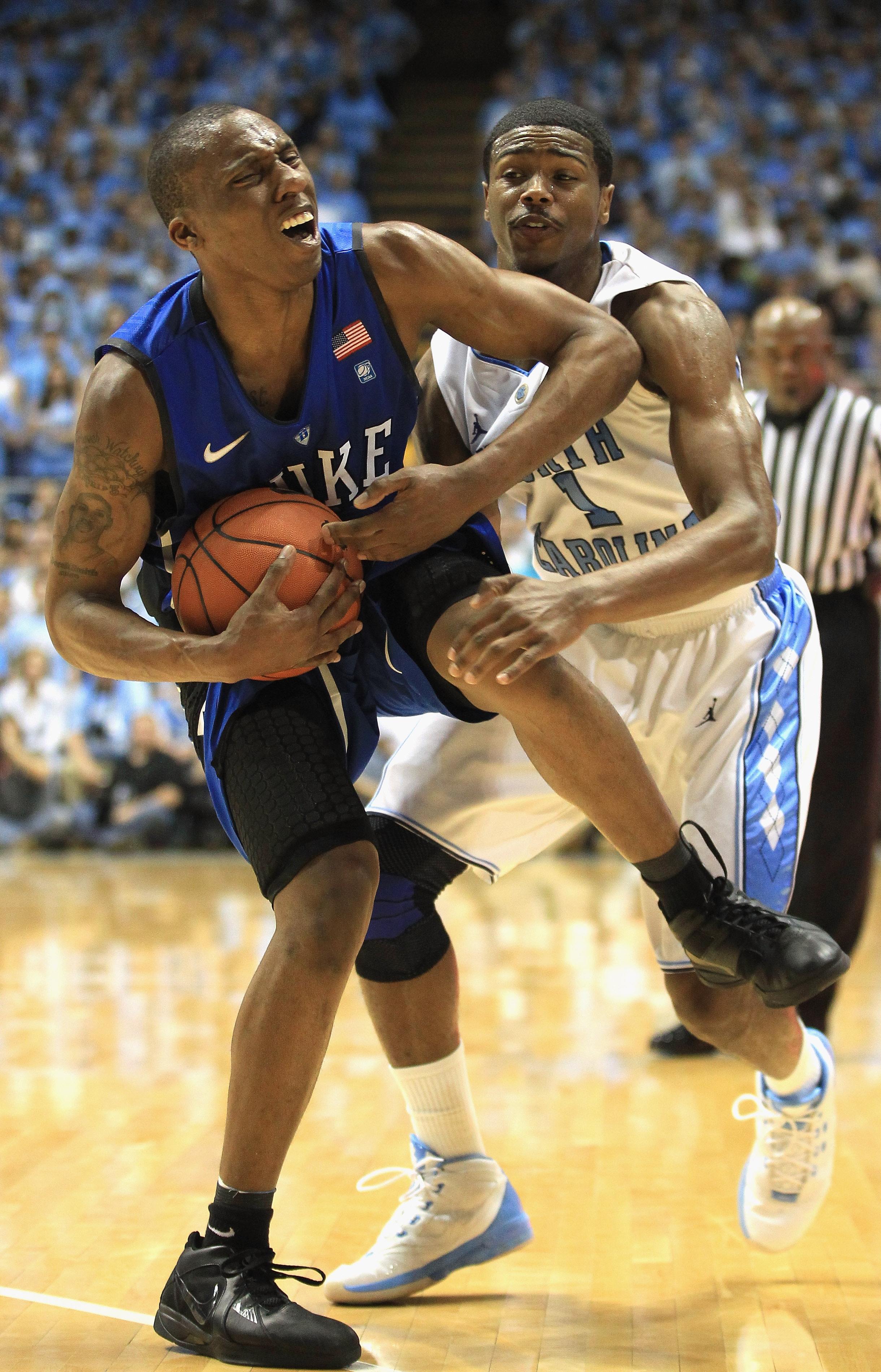 CHAPEL HILL, NC - MARCH 05:  Nolan Smith #2 of the Duke Blue Devils reacts to running into Dexter Strickland #1 of the North Carolina Tar Heels during their game at the Dean E. Smith Center on March 5, 2011 in Chapel Hill, North Carolina.  (Photo by Stree
