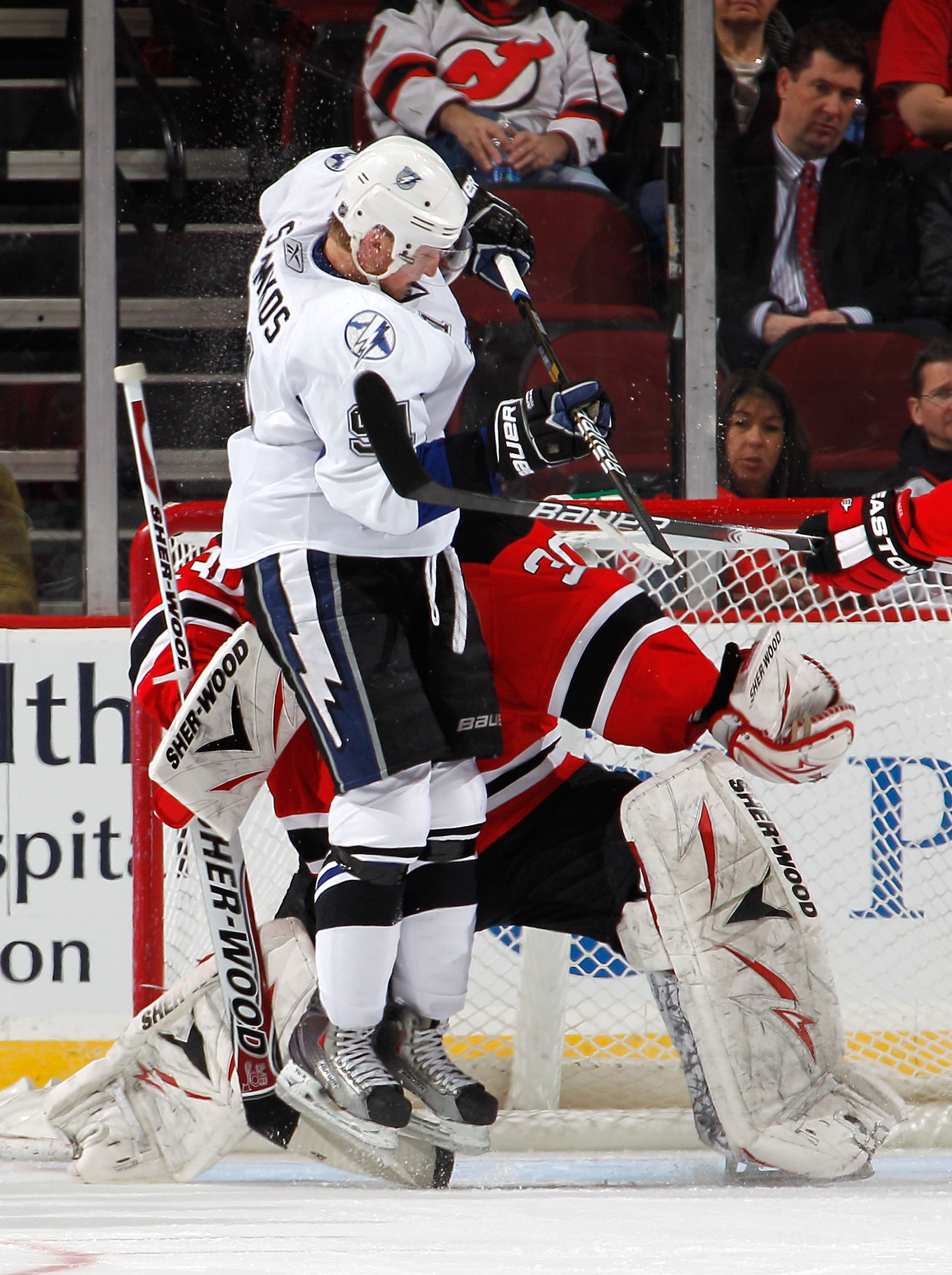 NEWARK, NJ - MARCH 02:  Steven Stamkos #91 of the Tampa Bay Lightning leaps to try to tip in a shot as he crashes into goalie Martin Brodeur #30 of the New Jersey Devils and receives a goaltender interference penalty during the second period of an NHL hoc
