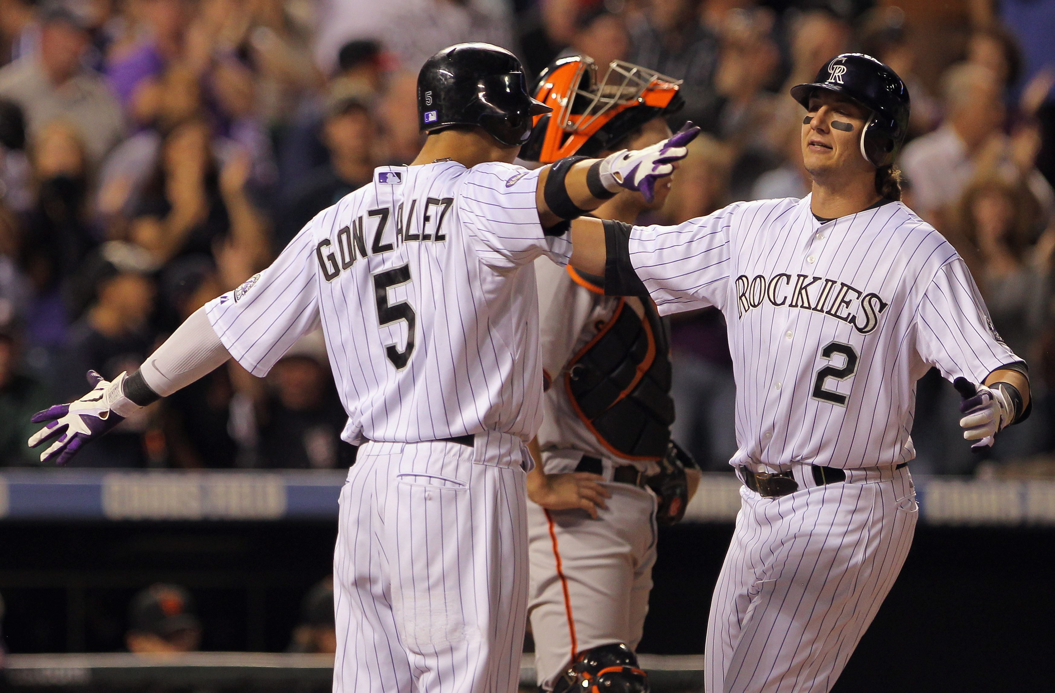 DENVER - SEPTEMBER 25:  Troy Tulowitzki #2 of the Colorado Rockies is welcomed home by Carlos Gonzalez #5 who scored on his two run homerun to give the Rockies a 5-4 lead over the San Francisco Giants in the fifth inning at Coors Field on September 25, 20