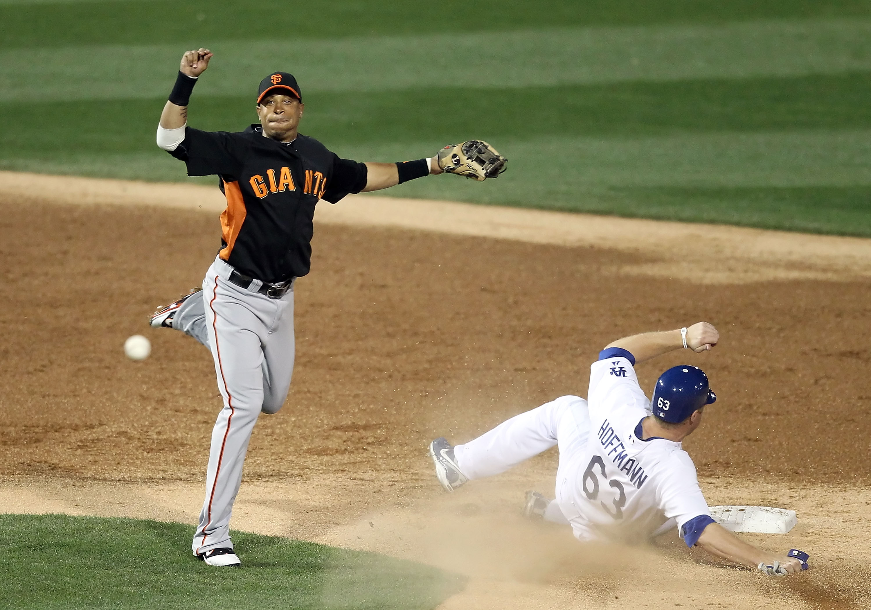 GLENDALE, AZ - MARCH 04:  Infielder Emmanuel Burriss #2 of the San Francisco Giants throws over the sliding Jamie Hoffmann #63 of the Los Angeles Dodgers to complete a double play during the second inning of the spring training game at Camelback Ranch on
