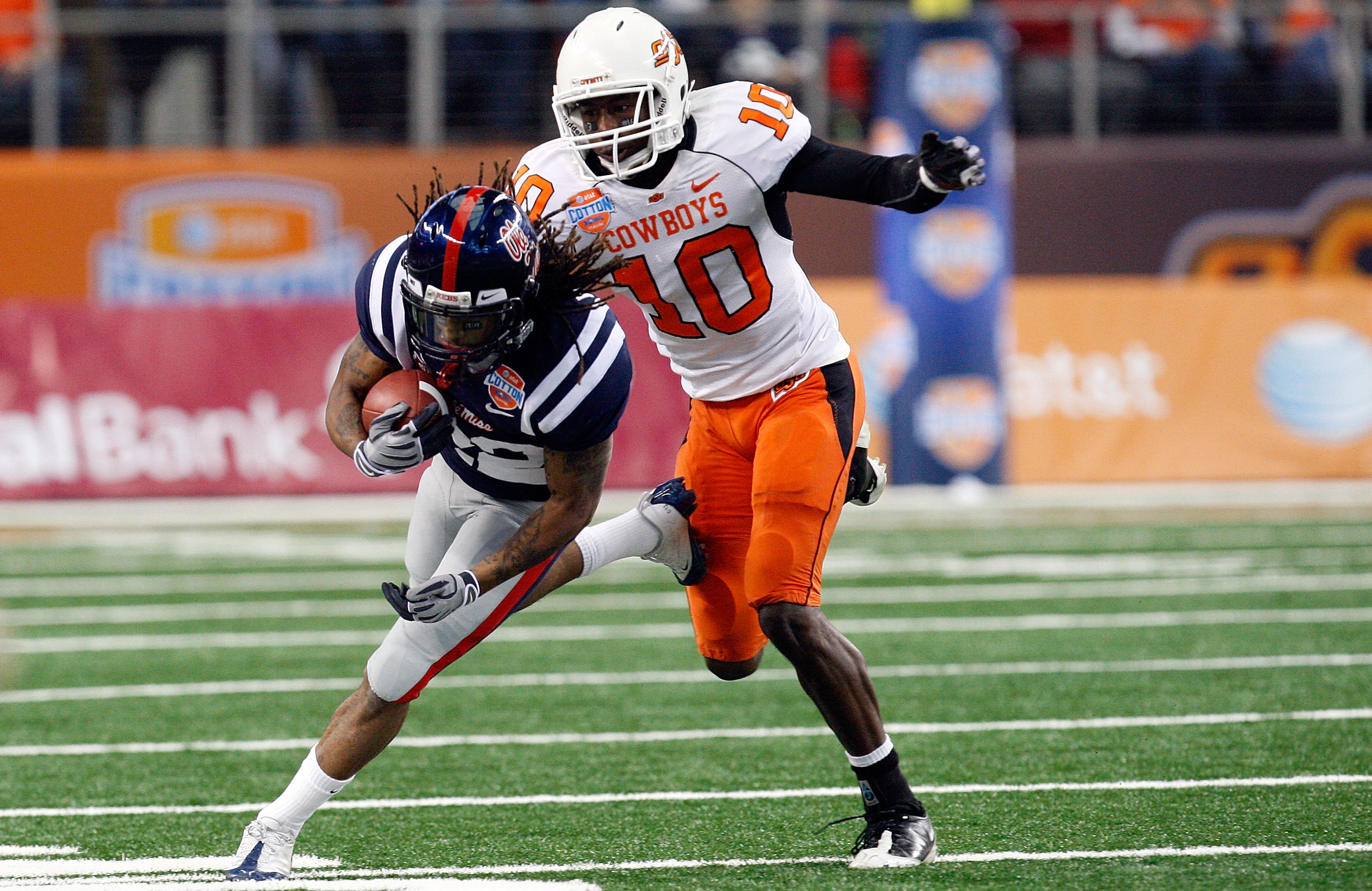 ARLINGTON, TX - JANUARY 02:  Dexter McCluster #22 of the Mississippi Rebels runs the ball against Markelle Martin #10 of the Oklahoma State Cowboys during the AT&T Cotton Bowl on January 2, 2010 at Cowboys Stadium in Arlington, Texas.  (Photo by Ronald Ma
