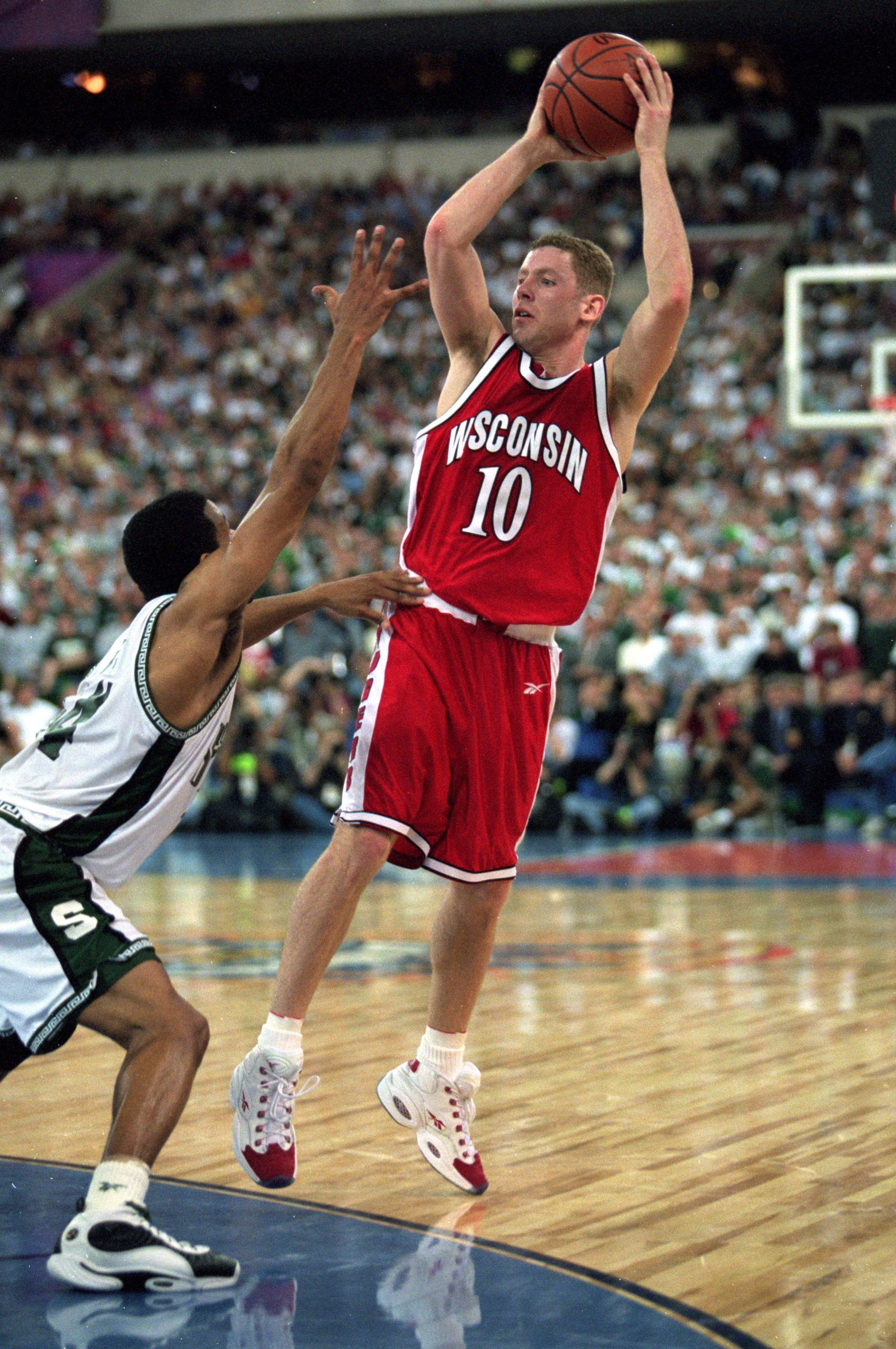 Jon Bryant #10 of the Wisconsin Badgers leaps to catch the ball during the NCAA Men''s Finals Four Game against the Michigan State Spartans at the RCA Dome in Indianapolis, Indiana. The Spartans defeated the Badgers 53-41.