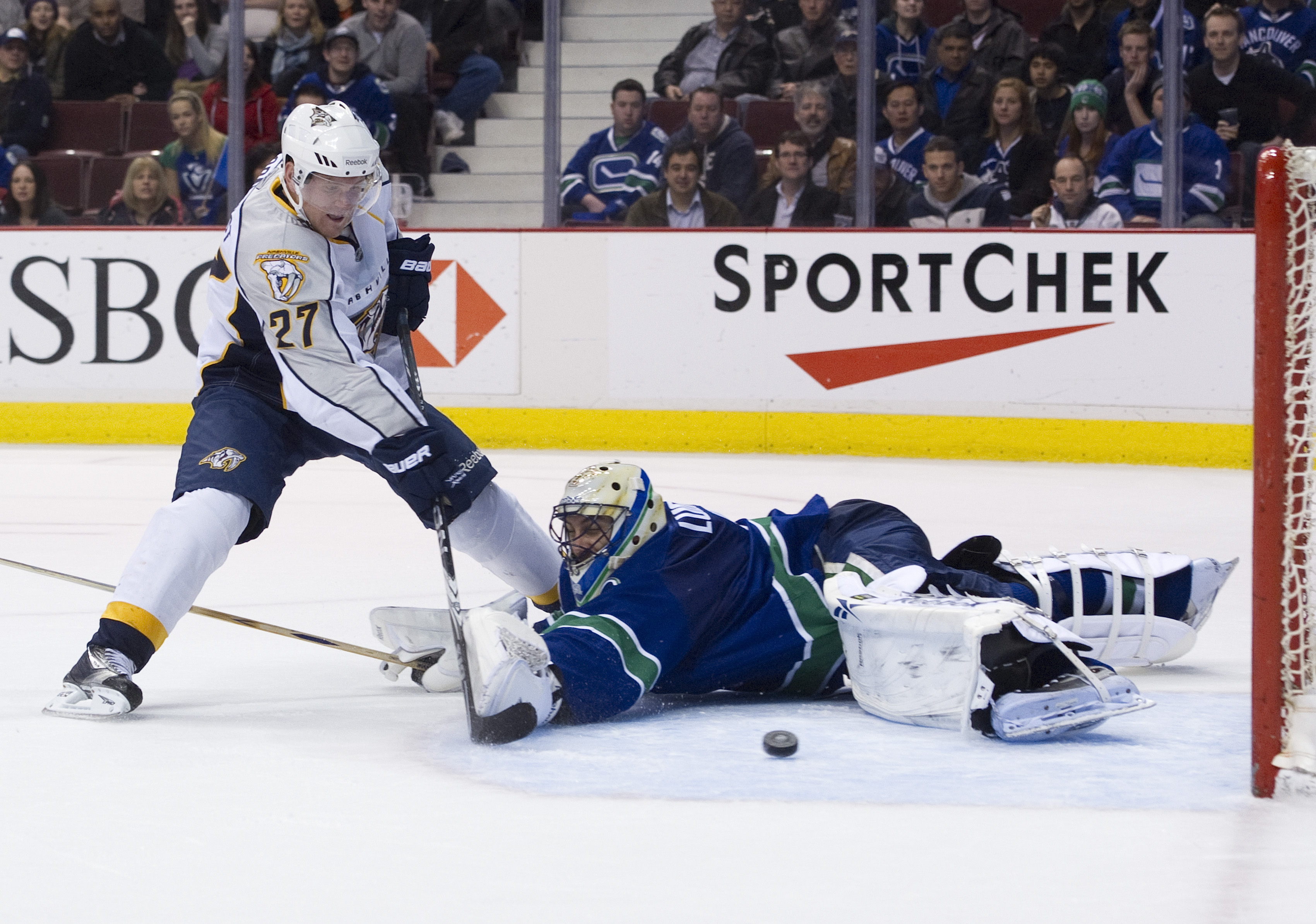 VANCOUVER, CANADA - MARCH 3: Patric Hornqvist #27 of the Nashville Predators slides the puck past goalie Roberto Luongo #1 of the Vancouver Canucks during the third period in NHL action on March 03, 2011 at Rogers Arena in Vancouver, British Columbia, Can