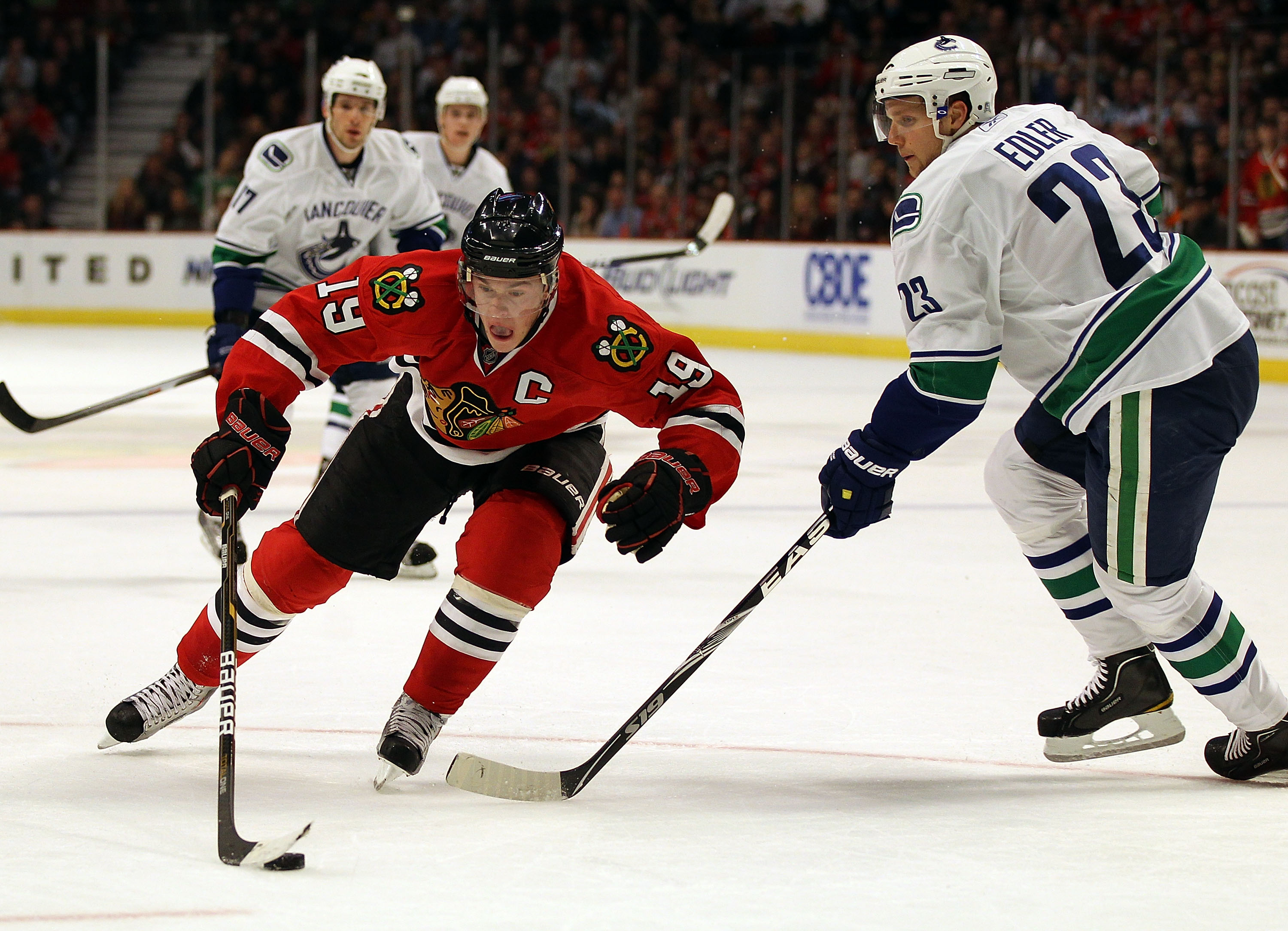CHICAGO, IL - DECEMBER 03: Jonathan Toews #19 of the Chicago Blackhawks controls the puck against Alexander Edler #23 of the Vancouver Canucks at the United Center on December 3, 2010 in Chicago, Illinois. The Canucks defeated the Blackhawks 3-0.  (Photo
