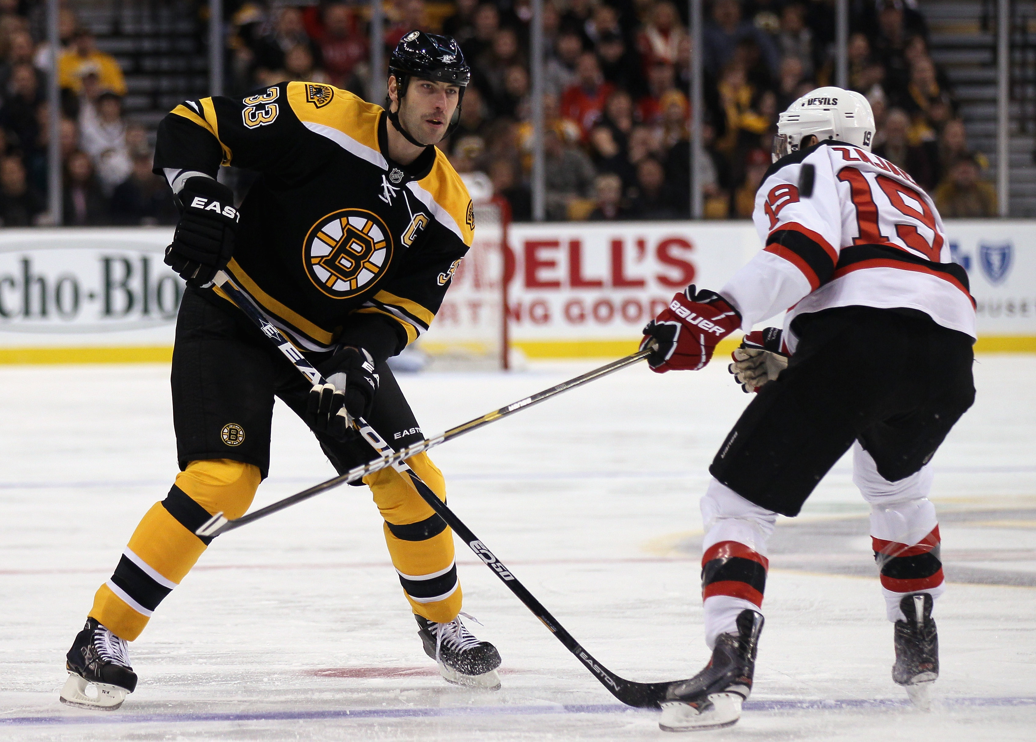 BOSTON - NOVEMBER 15: Zdeno Chara #33 of the Boston Bruins keeps the puck as Travis Zajac #19 of the New Jersey Devils defends on November 15, 2010 at the TD Garden in Boston, Massachusetts.  (Photo by Elsa/Getty Images)