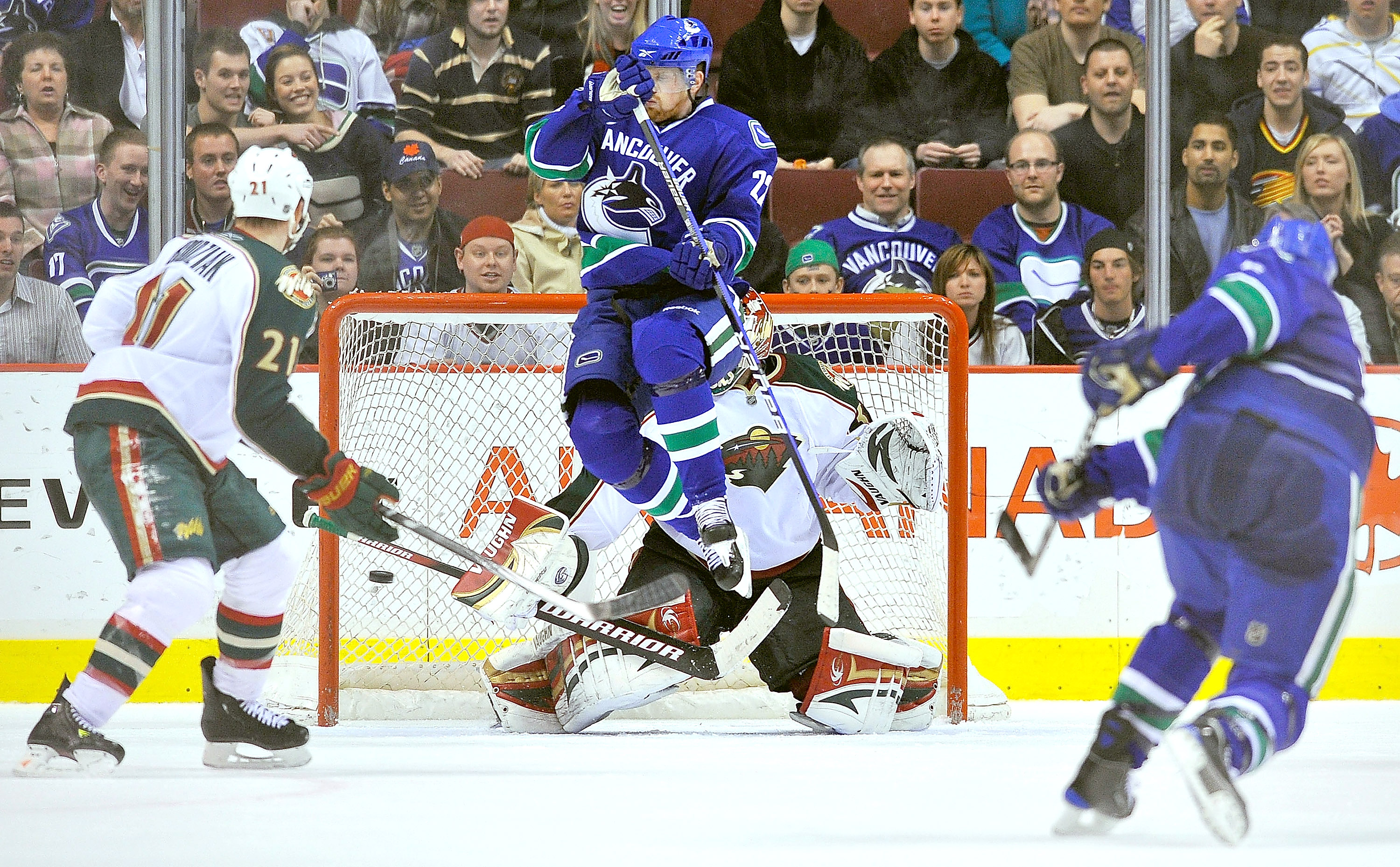 VANCOUVER, CANADA - APRIL 4: Daniel Sedin #22 of the Vancouver Canucks jumps out of the way of teammate Sami Salo's #6 shot as it find the back of the net past goalie Niklas Backstrom #32 of the Minnesota Wild during the overtime period of NHL action on A