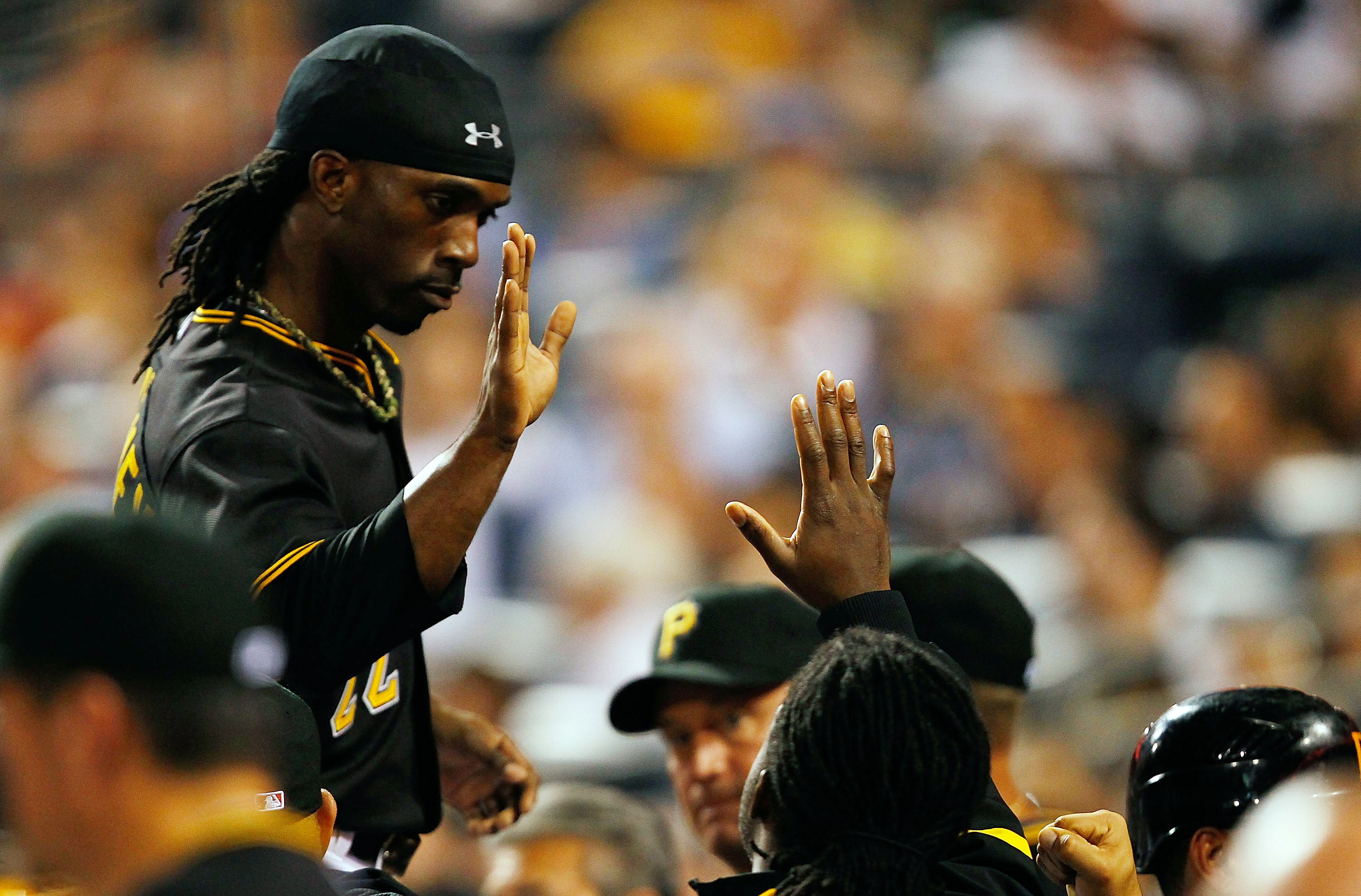 PITTSBURGH - SEPTEMBER 21:  Andrew McCutchen #22 of the Pittsburgh Pirates is congratulated by teammates in the dugout after scoring against the St. Louis Cardinals during the game on September 21, 2010 at PNC Park in Pittsburgh, Pennsylvania.  (Photo by