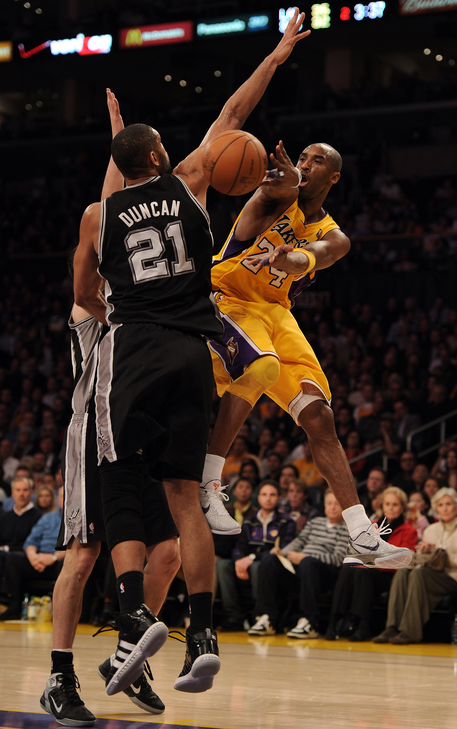 LOS ANGELES, CA - FEBRUARY 03:  Kobe Bryant #24 of the Los Angeles Lakers passes around Tim Duncan #21 of the San Antonio Spurs during the first half at Staples Center on February 3, 2011 in Los Angeles, California.  NOTE TO USER: User expressly acknowled