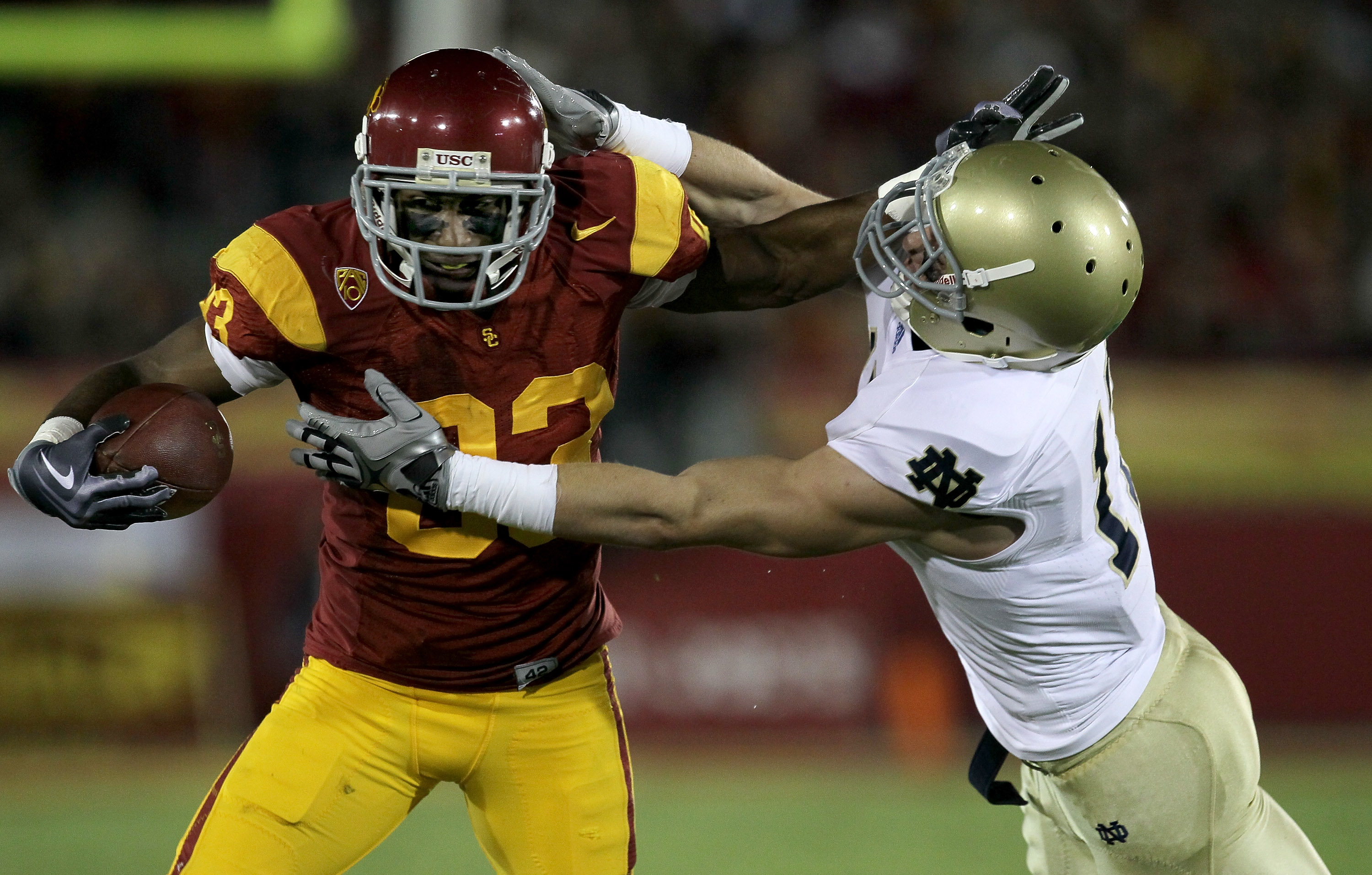 LOS ANGELES - NOVEMBER 27:  Wide receiver Ronald Johnson #83 of the USC Trojans carries ball against safety Zeke Motta #17 of the Notre Dame Fighting Irish at the Los Angeles Memorial Coliseum on November 27, 2010 in Los Angeles, California.   (Photo by S