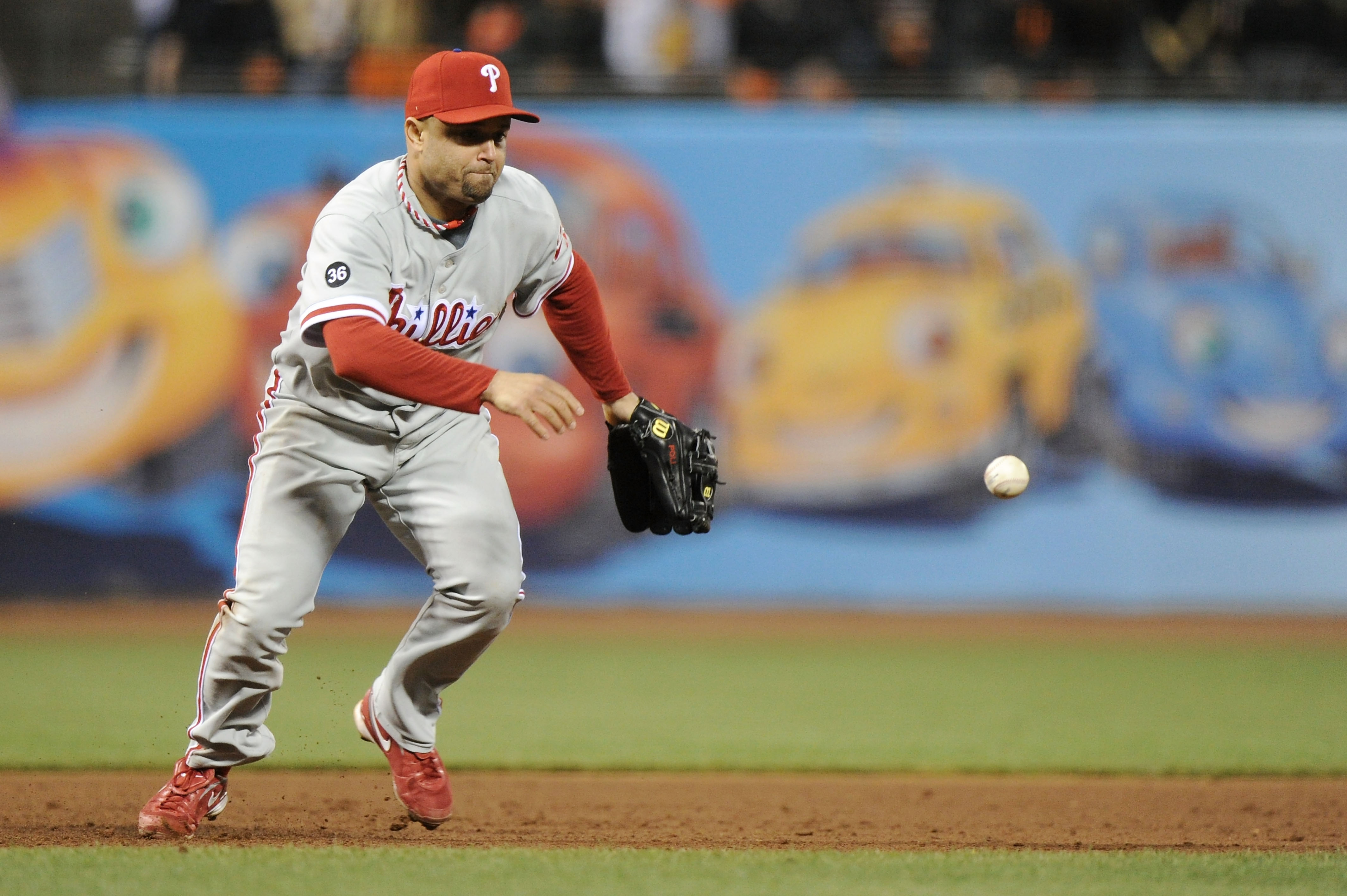 SAN FRANCISCO - OCTOBER 20:  Placido Polanco #27 of the Philadelphia Phillies misplays a ground ball hit by Edgar Renteria #16 of the San Francisco Giants in the fifth inning of Game Four of the NLCS during the 2010 MLB Playoffs at AT&T Park on October 20