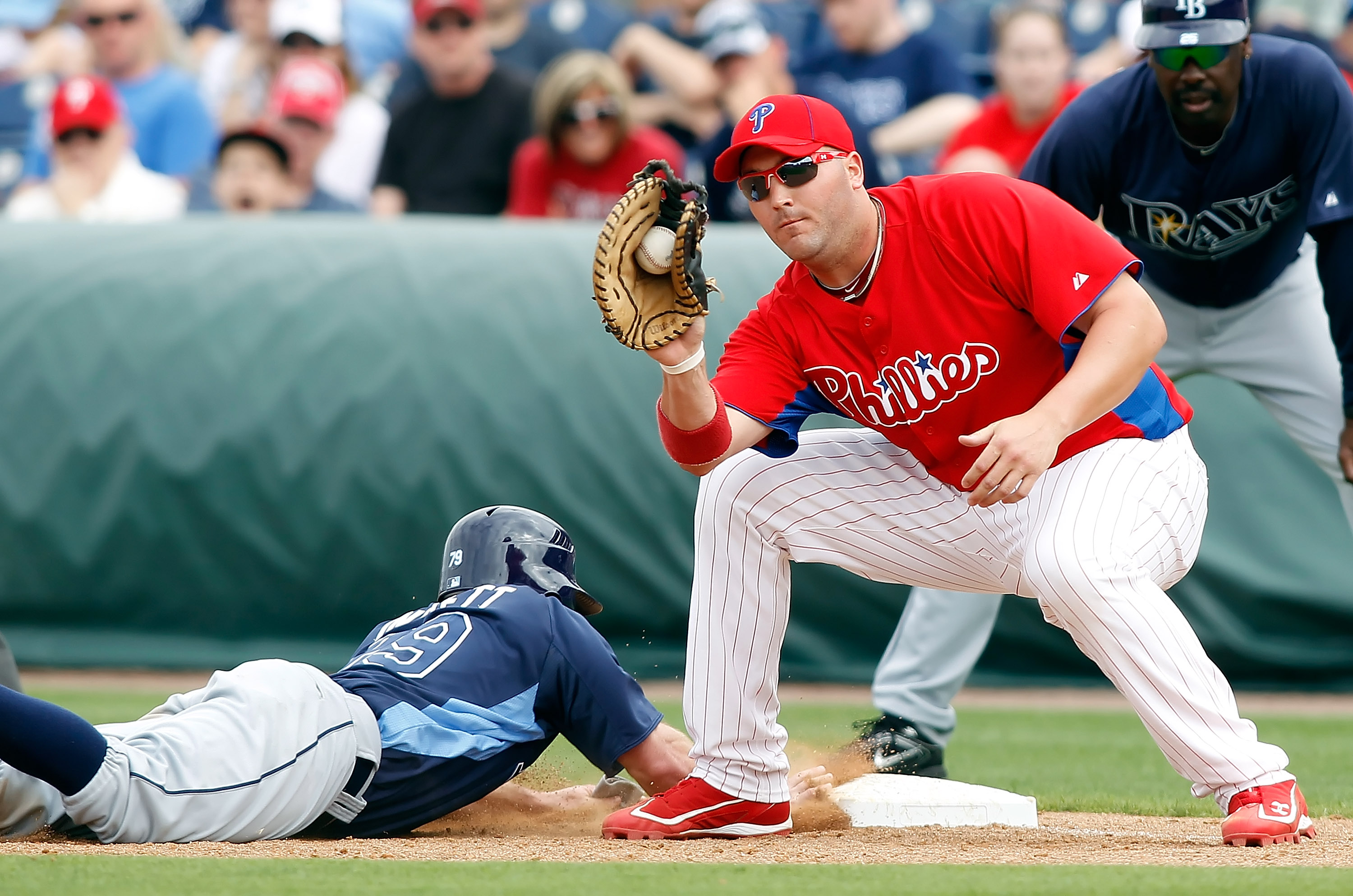CLEARWATER, FL - MARCH 06:  First baseman Matt Rizzotti #76 of the Philadelphia Phillies takes the throw at first as Joe Inglett #79 of the Tampa Bay Rays gets back safely during a Grapefruit League Spring Training Game at Bright House Field on March 6, 2