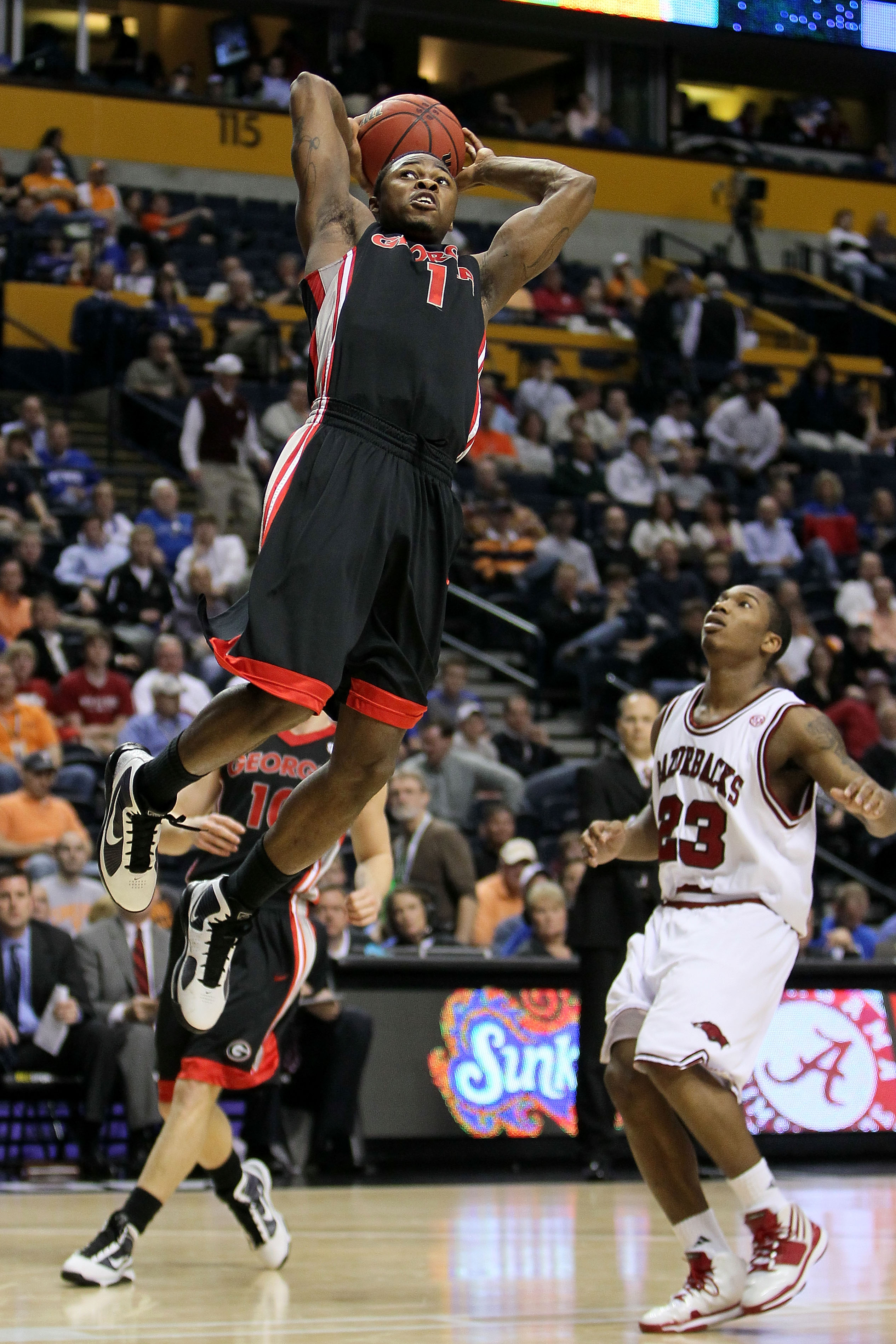 NASHVILLE, TN - MARCH 11:  Travis Leslie #1 of the Georgia Bulldogs goes up for a dunk attempt against Julysses Nobles #23 of the Arkanasas Razorbacks during the first round of the SEC Men's Basketball Tournament at the Bridgestone Arena on March 11, 2010