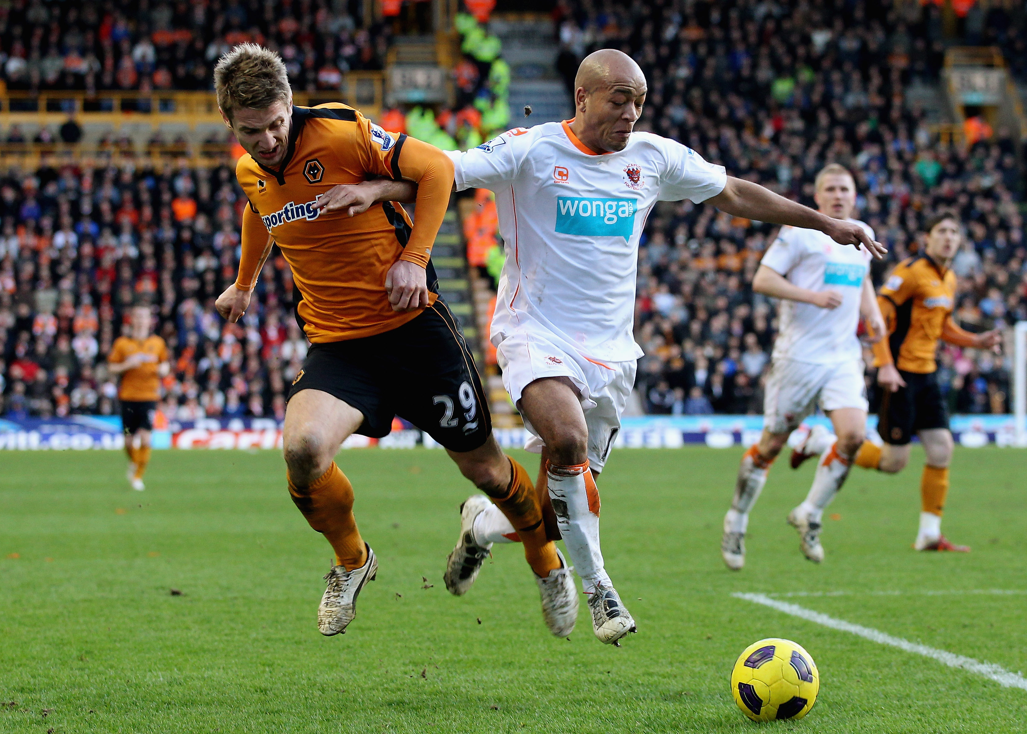 WOLVERHAMPTON, ENGLAND - FEBRUARY 26:  Kevin Doyle of Wolves (L) in action with Alex Baptiste of Blackpool during the Barclays Premier League match between Wolverhampton Wanderers and Blackpool at Molineux on February 26, 2011 in Wolverhampton, England.