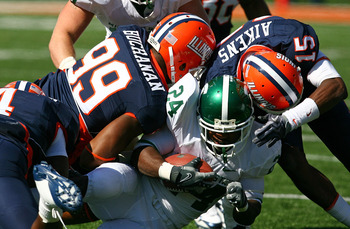 CHAMPAIGN, IL - OCTOBER 10: Walter Aikens #15 and Michael Buchanan #99 of the Illinois Fighting Illini tackle Caulton Ray #24 of the Michigan State Spartans on October 10, 2009 at Memorial Stadium at the University of Illinois in Champaign, Illinois. Mich
