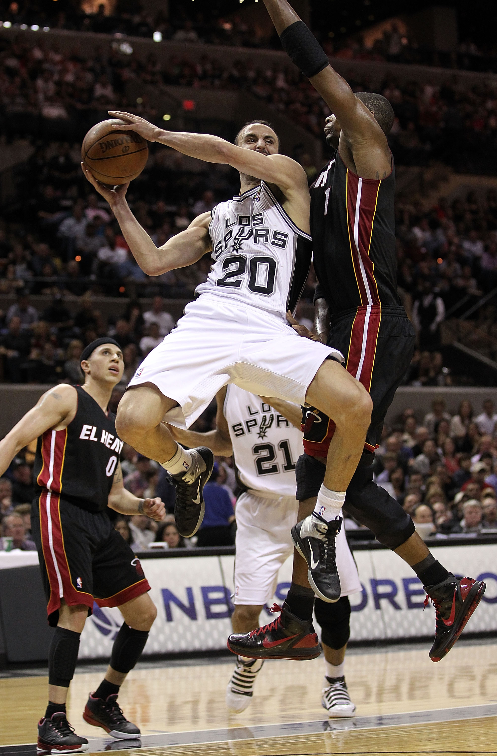 SAN ANTONIO, TX - MARCH 04:  Guard Manu Ginobili #20 of the San Antonio Spurs drives the lane against Chris Bosh #1 of the Miami Heat at AT&T Center on March 4, 2011 in San Antonio, Texas.   NOTE TO USER: User expressly acknowledges and agrees that, by do