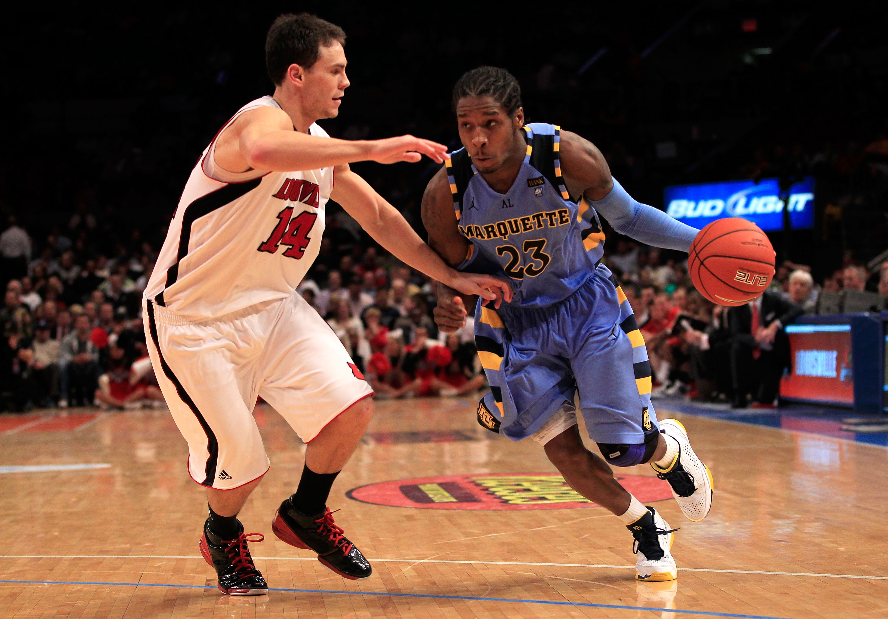 NEW YORK, NY - MARCH 10: Dwight Buycks #23 of the Marquette Golden Eagles drives with the ball against Kyle Kuric #14 of the Louisville Cardinals during the quarterfinals of the 2011 Big East Men's Basketball Tournament presented by American Eagle Outfitt