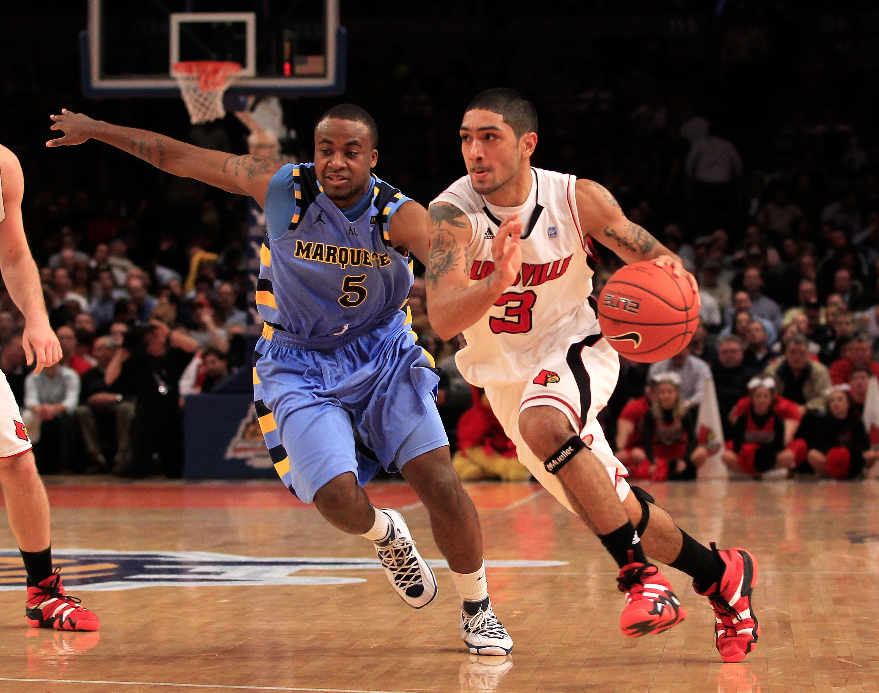 NEW YORK, NY - MARCH 10:  Peyton Siva #3 of the Louisville Cardinals brings the ball up court against Junior Cadougan #5 of the Marquette Golden Eagles during the quarterfinals of the 2011 Big East Men's Basketball Tournament presented by American Eagle O