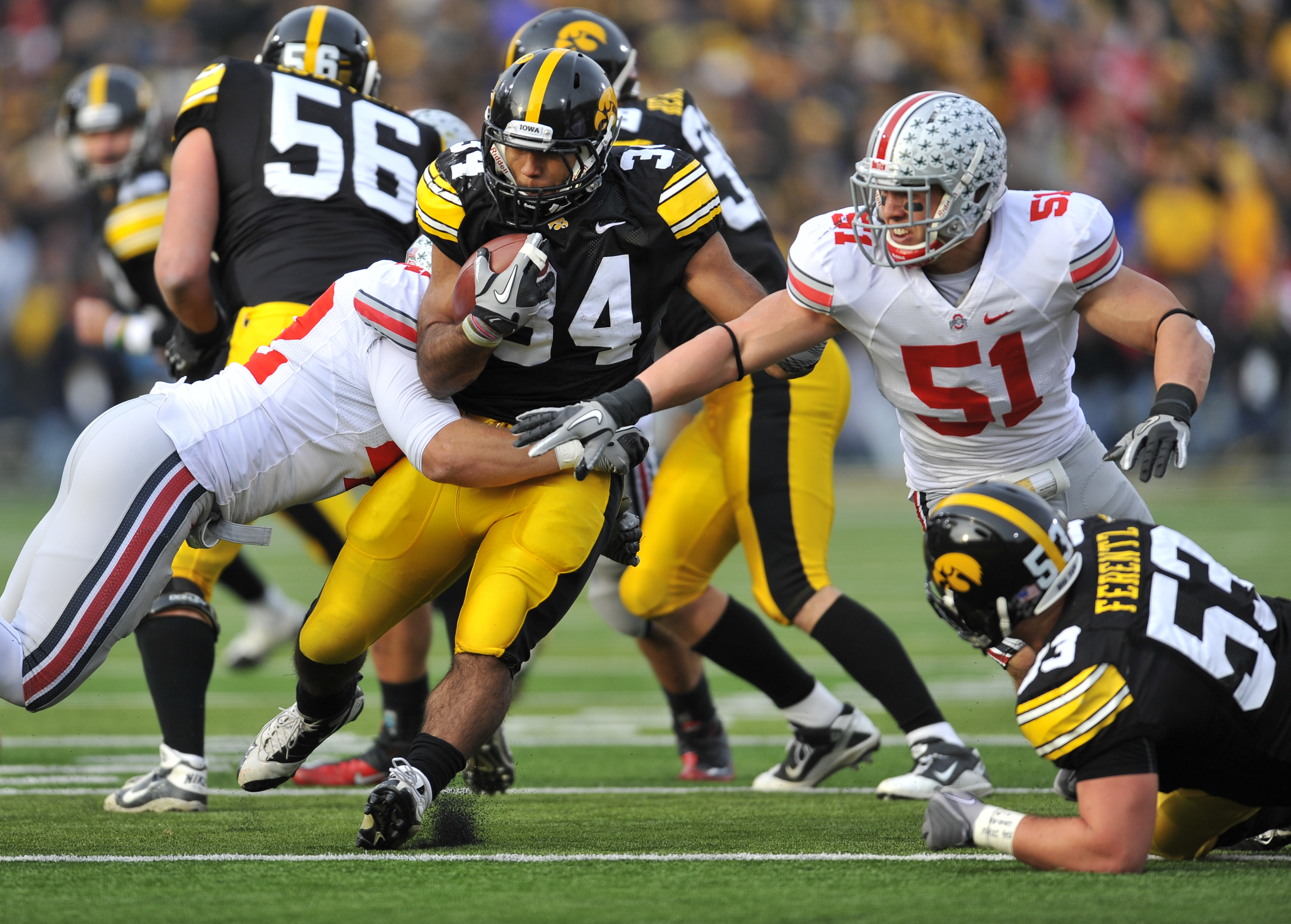 IOWA CITY, IA - NOVEMBER 20:  Running back Marcus Coker #34 of the University of Iowa Hawkeyes is tackled by line backer Andrew Sweat #42 of the Ohio State Buckeyes during the second half of play at Kinnick Stadium on November 20, 2010 in Iowa City, Iowa.