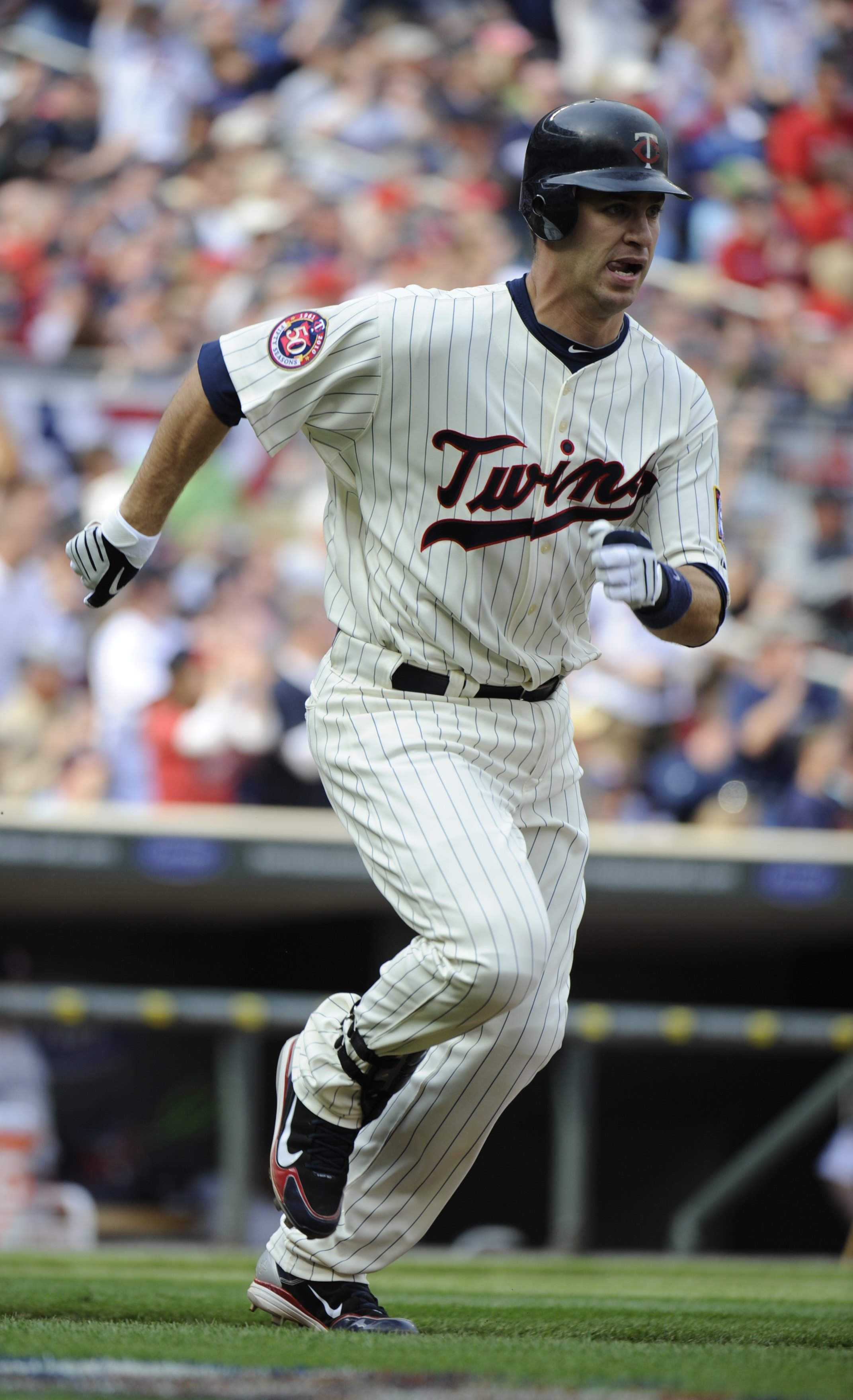 MINNEAPOLIS, MN - APRIL 12: Joe Mauer #7 of the Minnesota Twins runs towards first base after hitting an RBI double in the second inning against the Boston Red Sox during the Twins home opener at Target Field on April 12, 2010 in Minneapolis, Minnesota. (