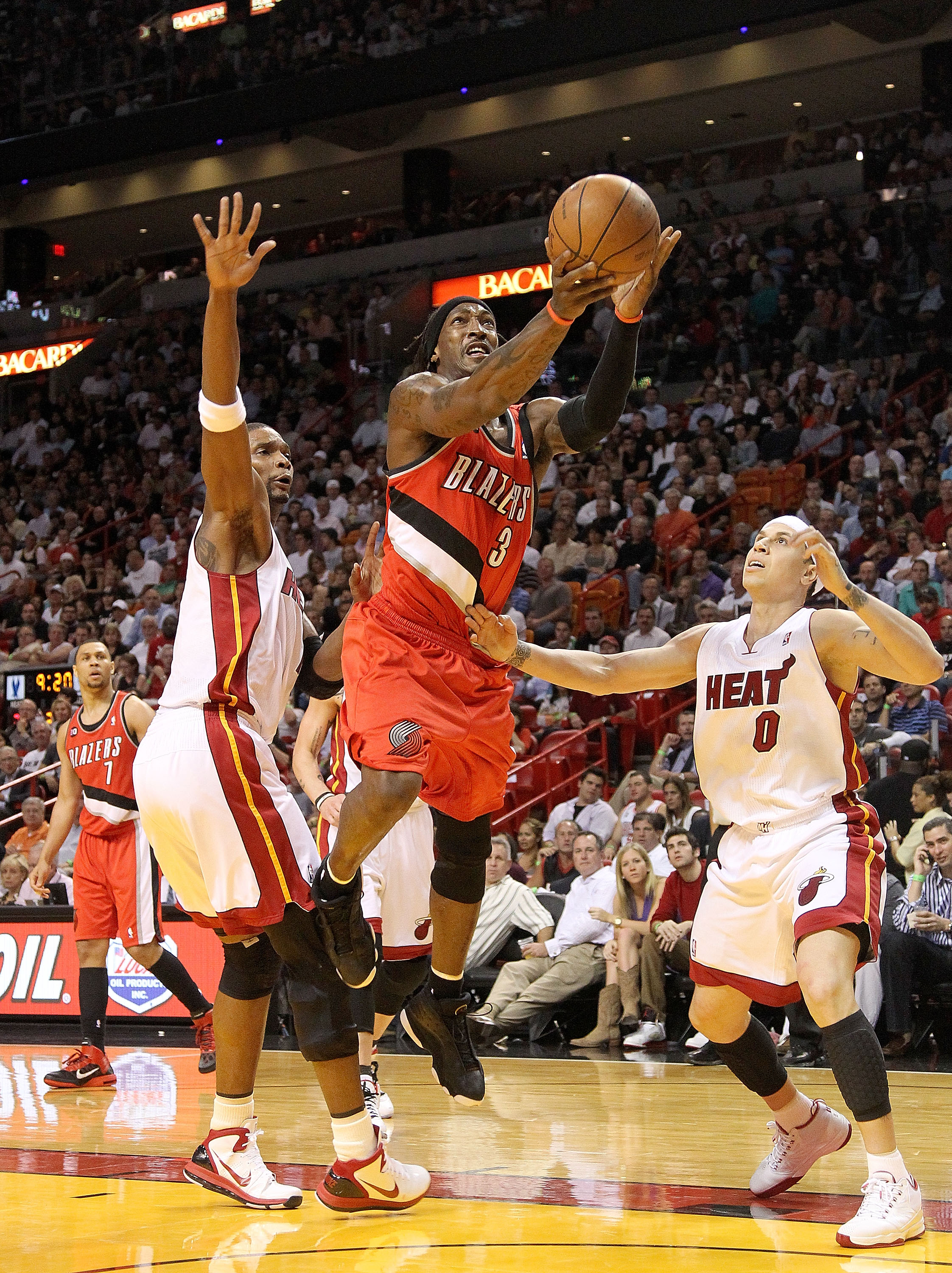 MIAMI, FL - MARCH 08: Gerald Wallace #3 of the Portland Trail Blazers splits through Chris Bosh #1 and Mike Bibby #0 of the Miami Heat during a game at American Airlines Arena on March 8, 2011 in Miami, Florida. NOTE TO USER: User expressly acknowledges a