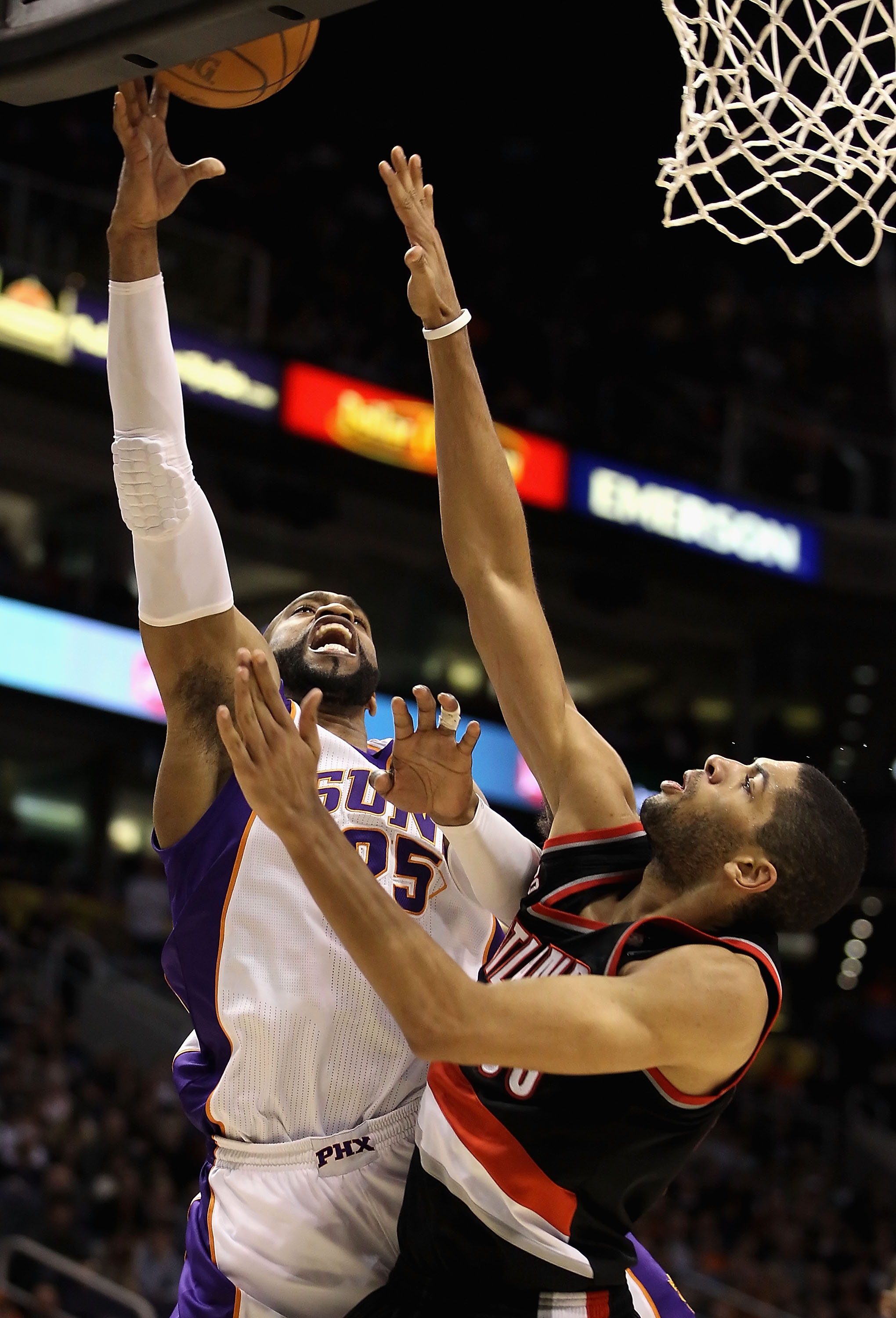 PHOENIX, AZ - JANUARY 14:  Vince Carter #25 of the Phoenix Suns lays up a shot over Nicolas Batum #88 of the Portland Trail Blazers during the NBA game at US Airways Center on January 14, 2011 in Phoenix, Arizona. The Suns defeated the Trail Blazers 115-1