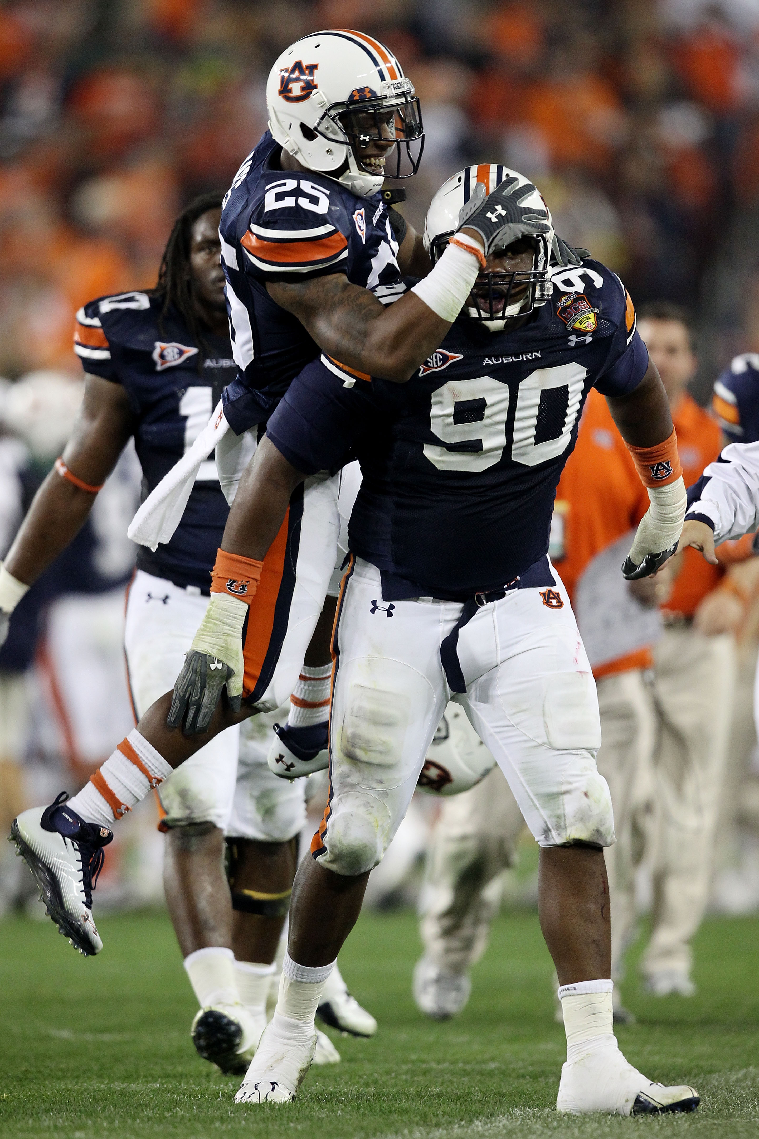 GLENDALE, AZ - JANUARY 10:  Nick Fairley #90 of the Auburn Tigers is congratulated by Daren Bates #25 on a sack against the Oregon Ducks during the Tostitos BCS National Championship Game at University of Phoenix Stadium on January 10, 2011 in Glendale, A