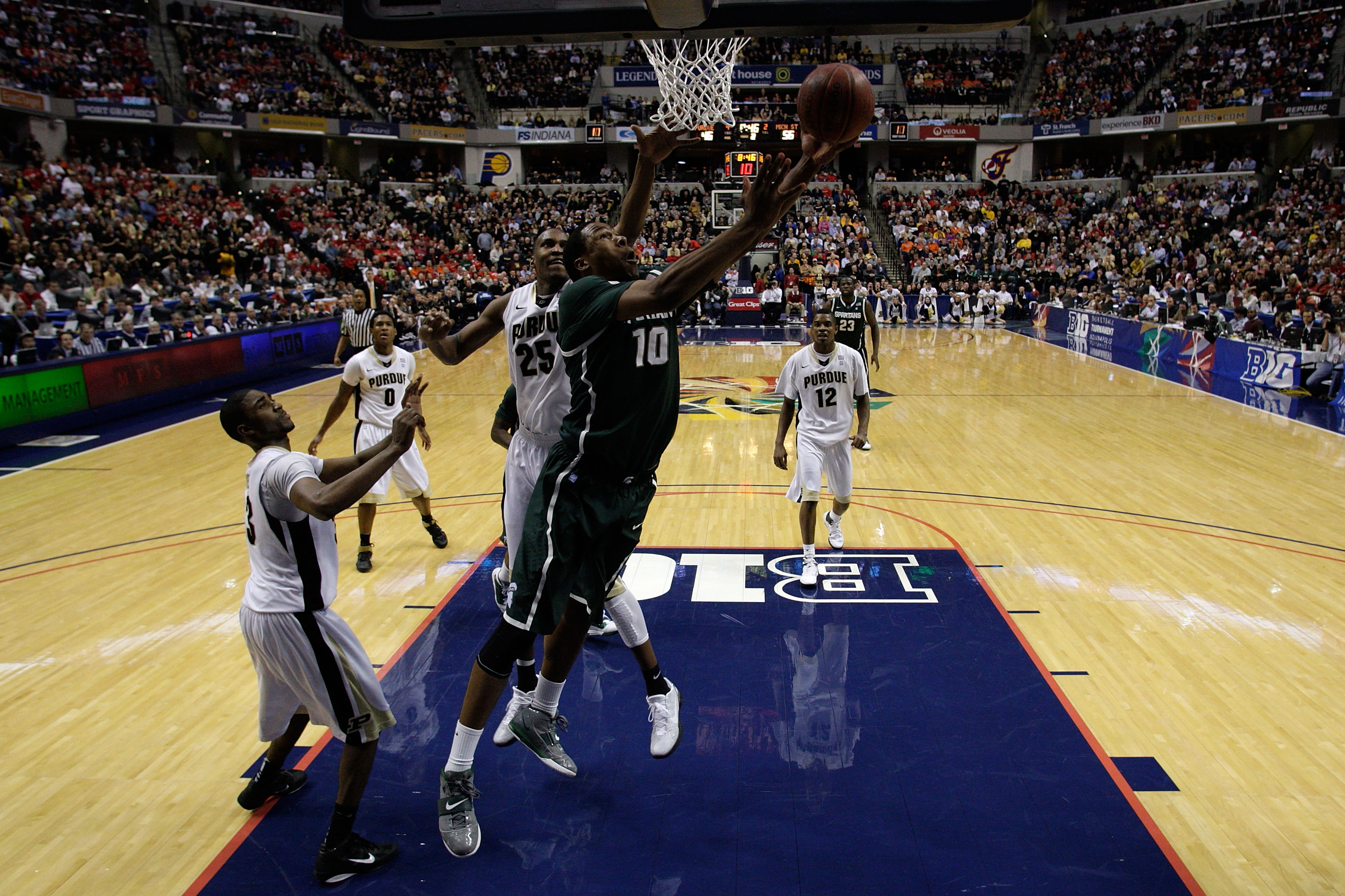 INDIANAPOLIS, IN - MARCH 11:  Delvon Roe #10 of the Michigan State Spartans drives for a shot attempt against JaJuan Johnson #25 of the Purdue Boilermakers during the quarterfinals of the 2011 Big Ten Men's Basketball Tournament at Conseco Fieldhouse on M